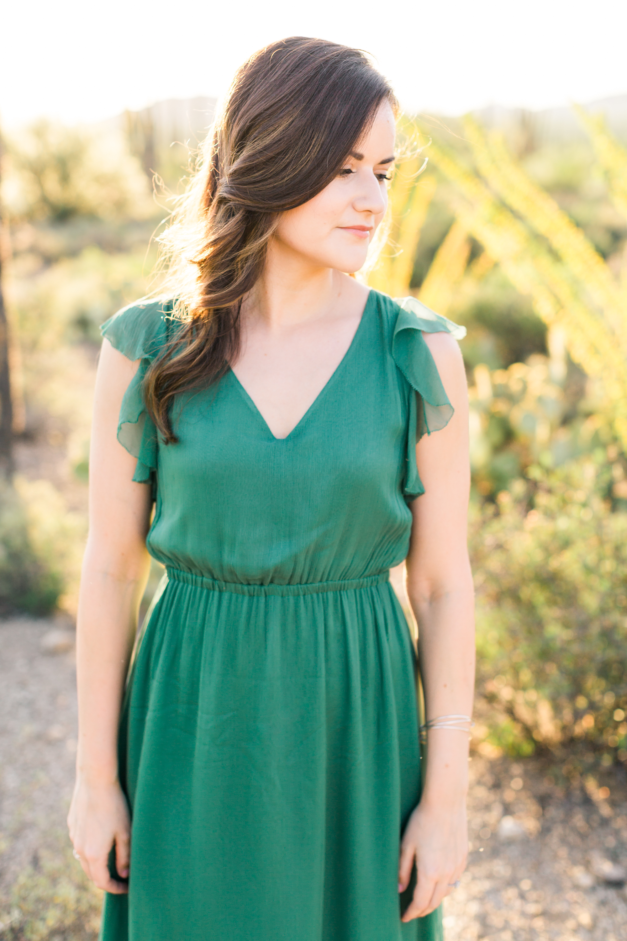 Beautiful girl in gorgeous green dress with the desert in the background.