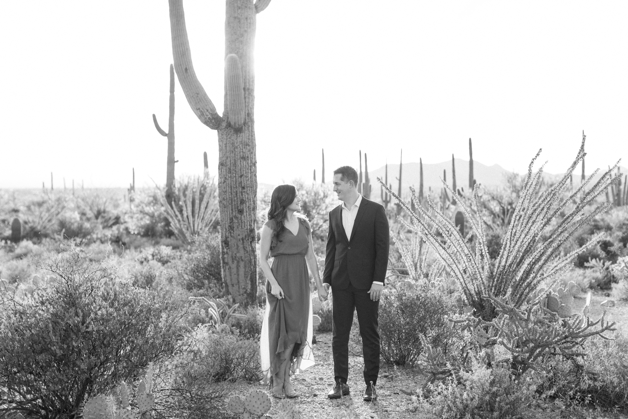 Black and white photo of a couple holding hands, looking at each other at their desert engagement session.