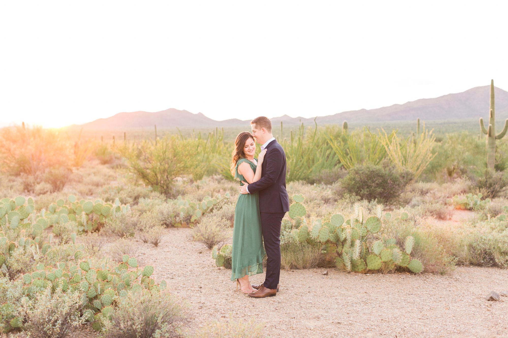 Engagement photo of an adorable couple hugging each other with the Tucson sunset and gorgeous desert in the background at golden hour.