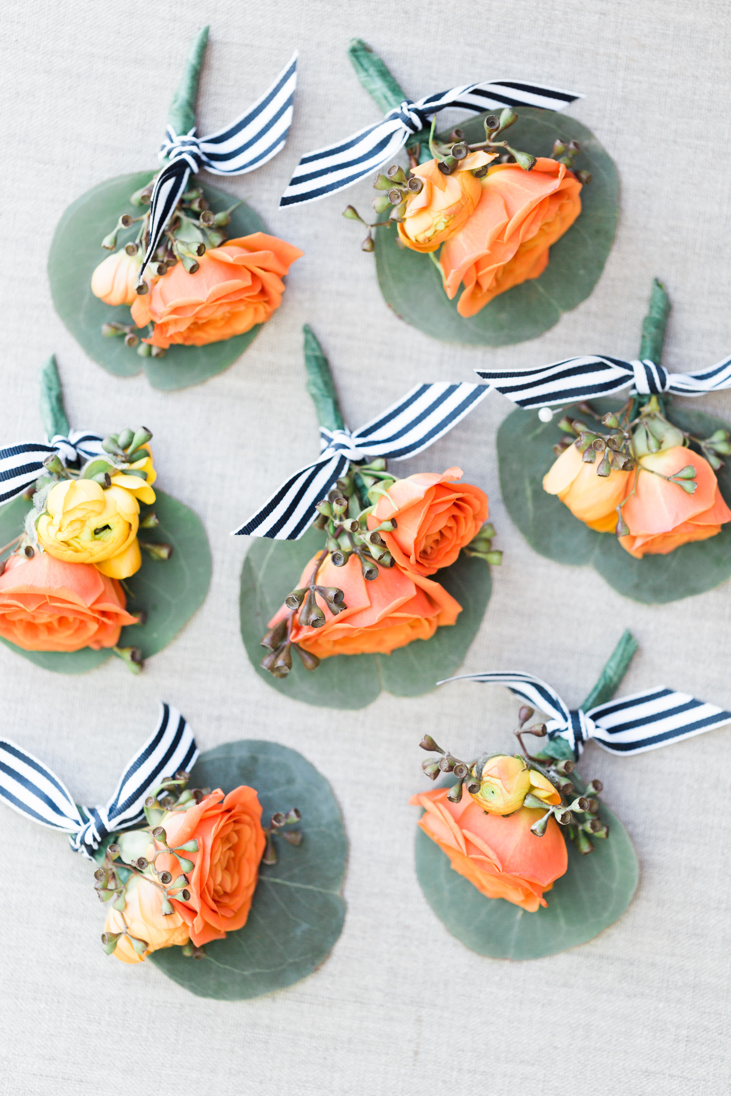 Orange and salmon rose boutonnieres with striped navy and white ribbon. So dreamy!