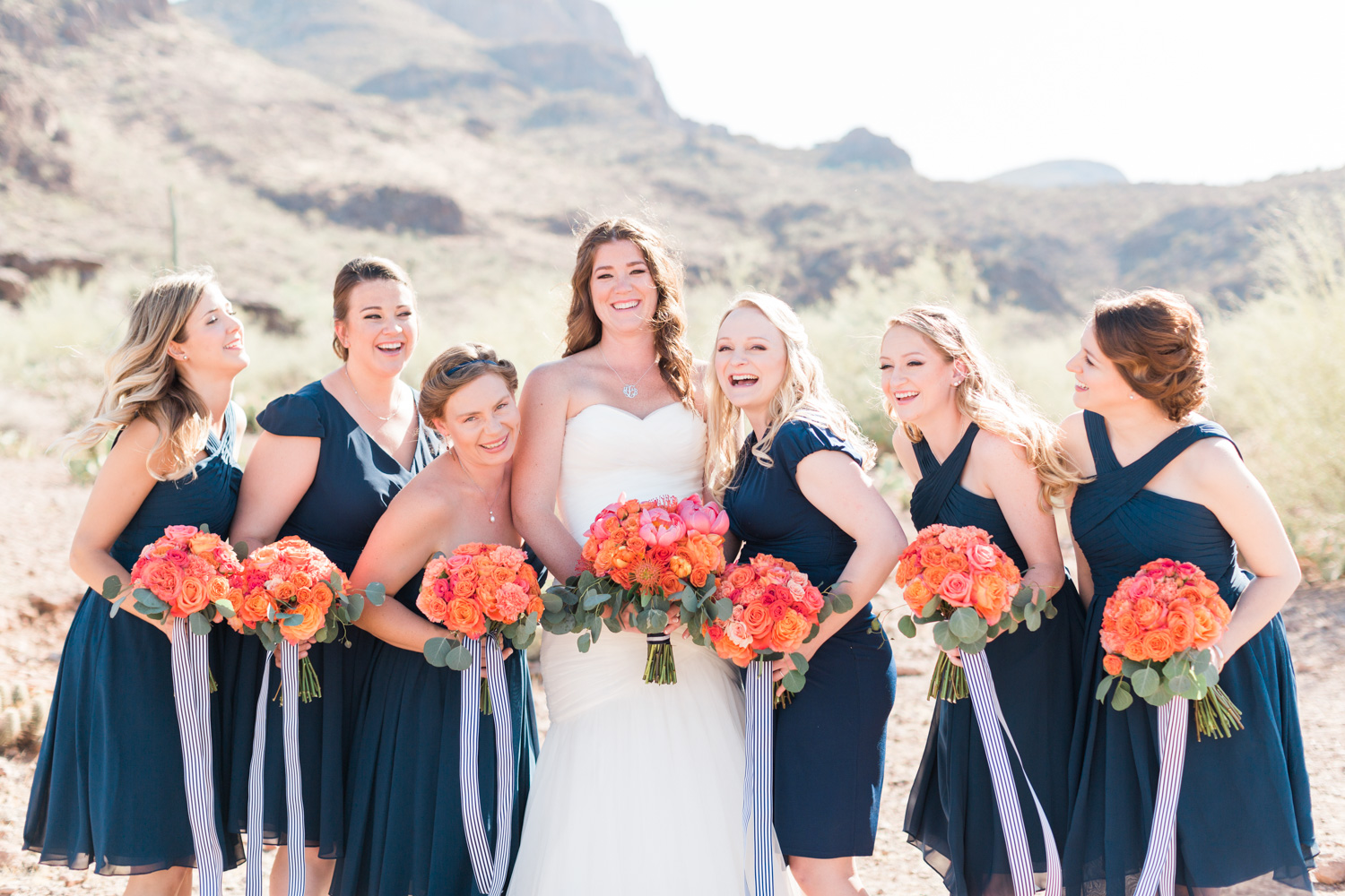 Bride and her bridesmaids in navy dresses with salmon and pink bouquets. Tucson mountains in background