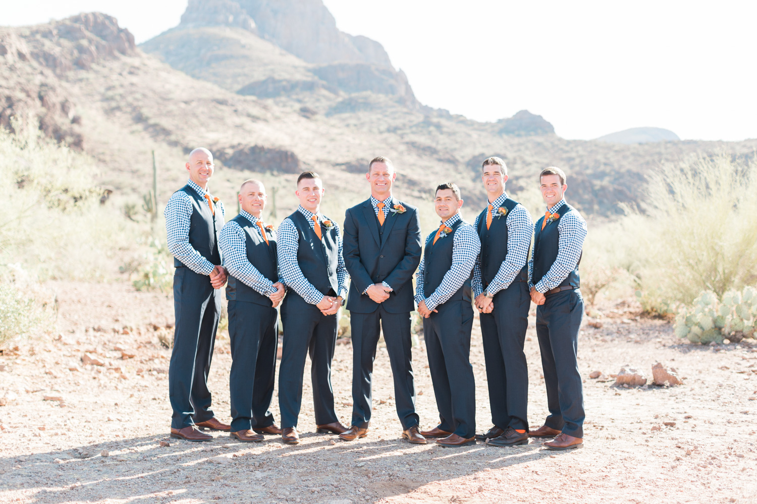 Handsome Groomsmen in navy gingham shirts with orange ties and navy suits. Beautiful mountain views in the background!