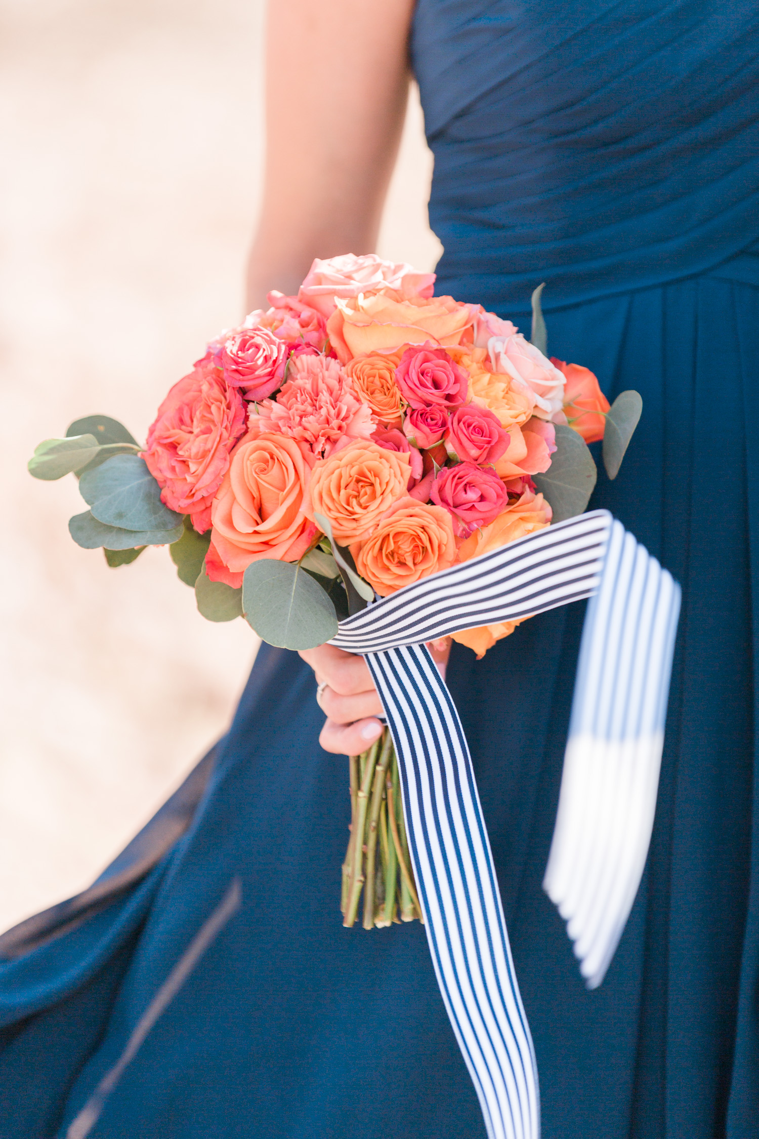 Beautiful salmon and pink bridesmaid bouquet with ribbon blowing in the wind.