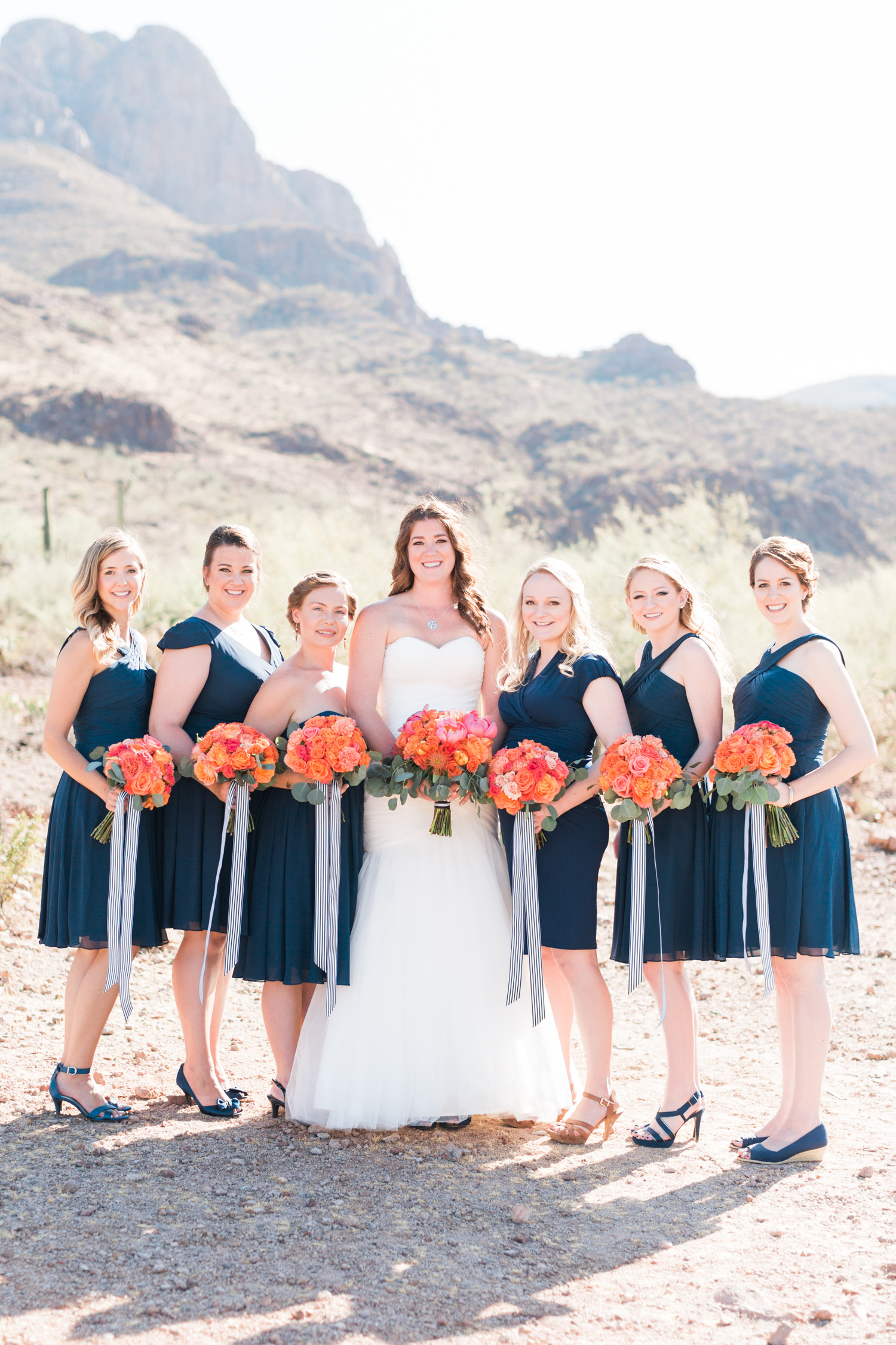 Beautiful bride and bridesmaids in navy with salmon bouquets, smiling at the camera.
