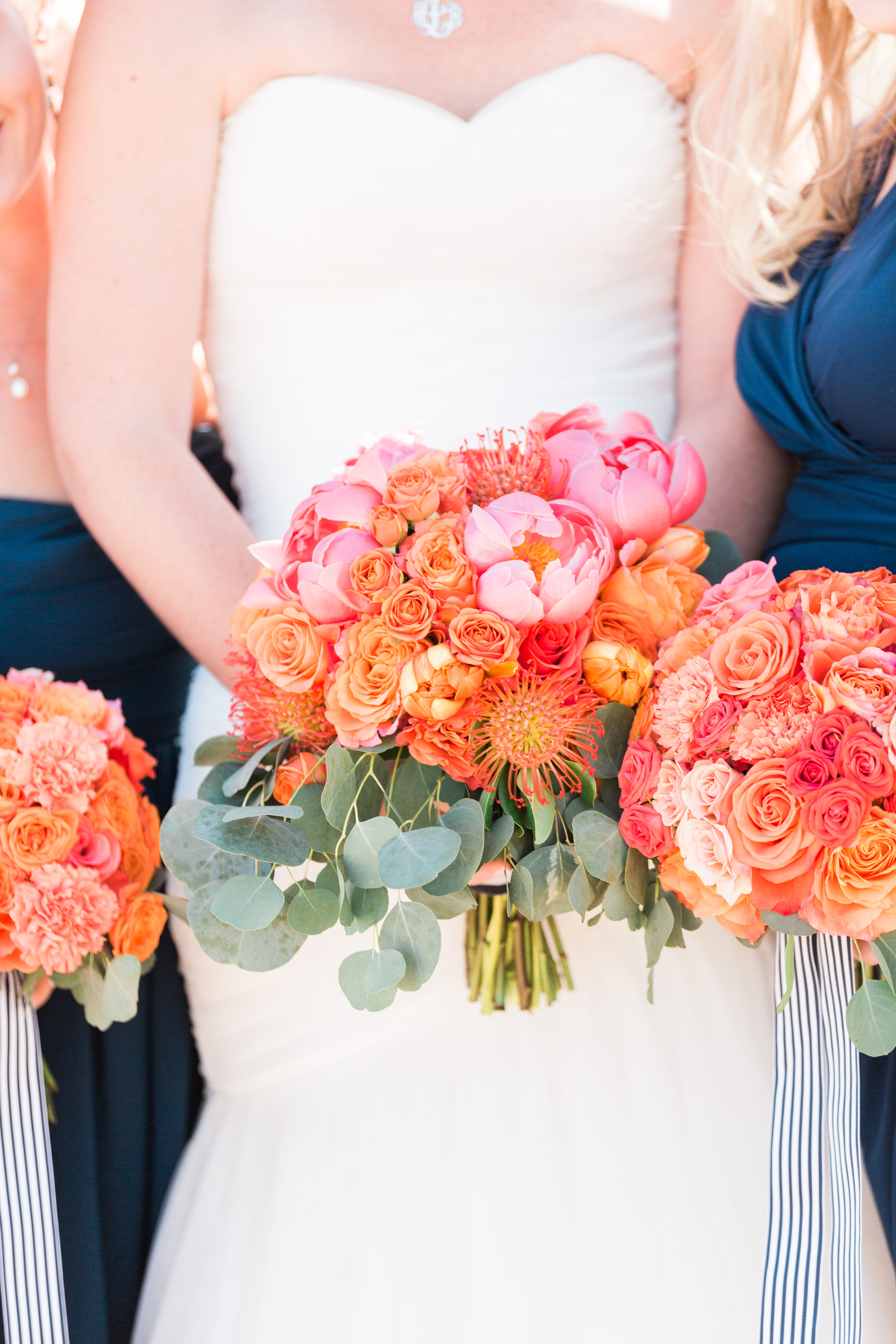 Bride in strapless sweetheart neckline wedding dress holding bouquet. Beautiful bouquet with pink peonies, salmon roses, orange protea pincushion and eucalyptus.