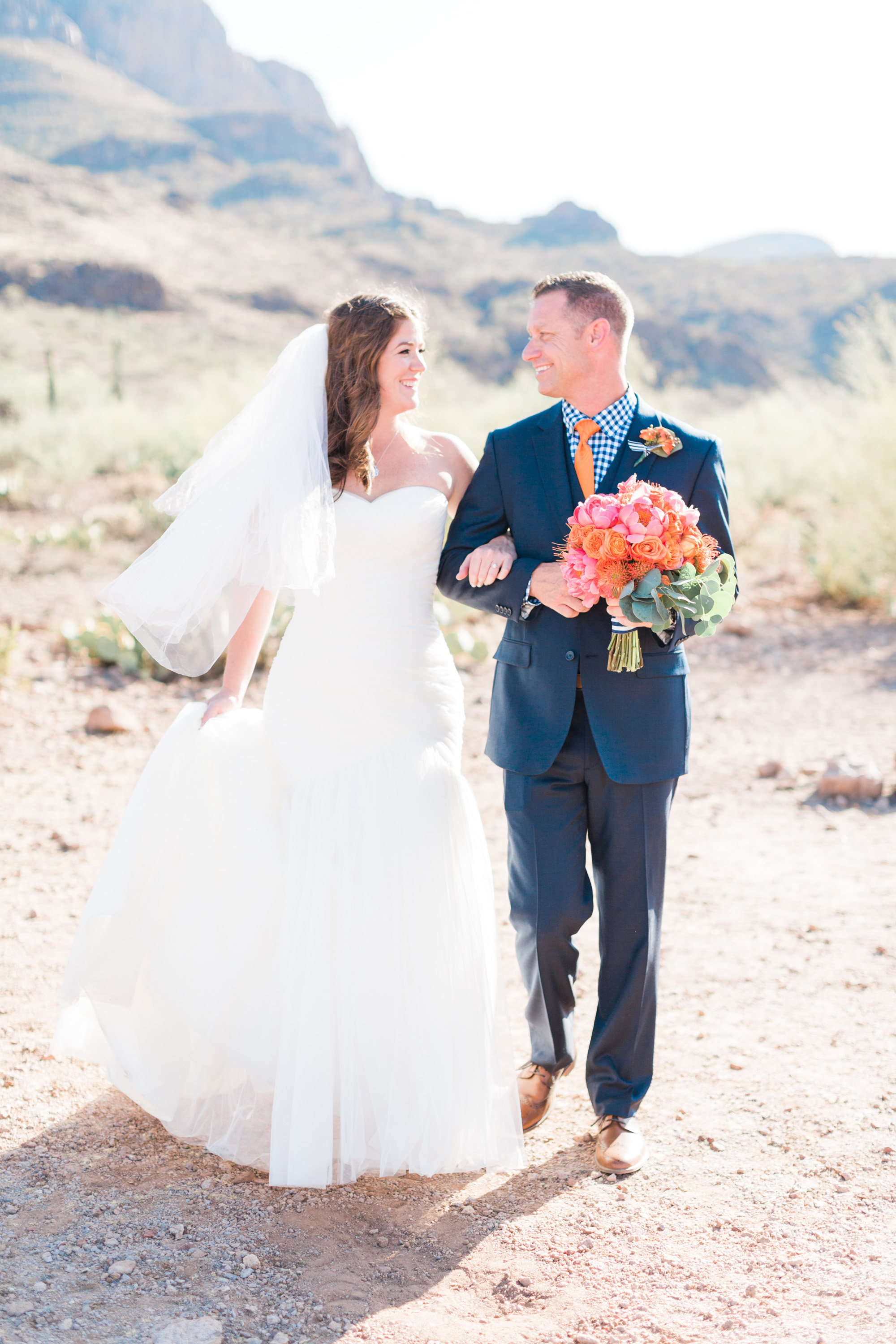 Bride and groom walking towards the camera. Groom holding bouquet and bride holding her dress. Love the light and airy feel of this beautiful Tucson summer wedding.