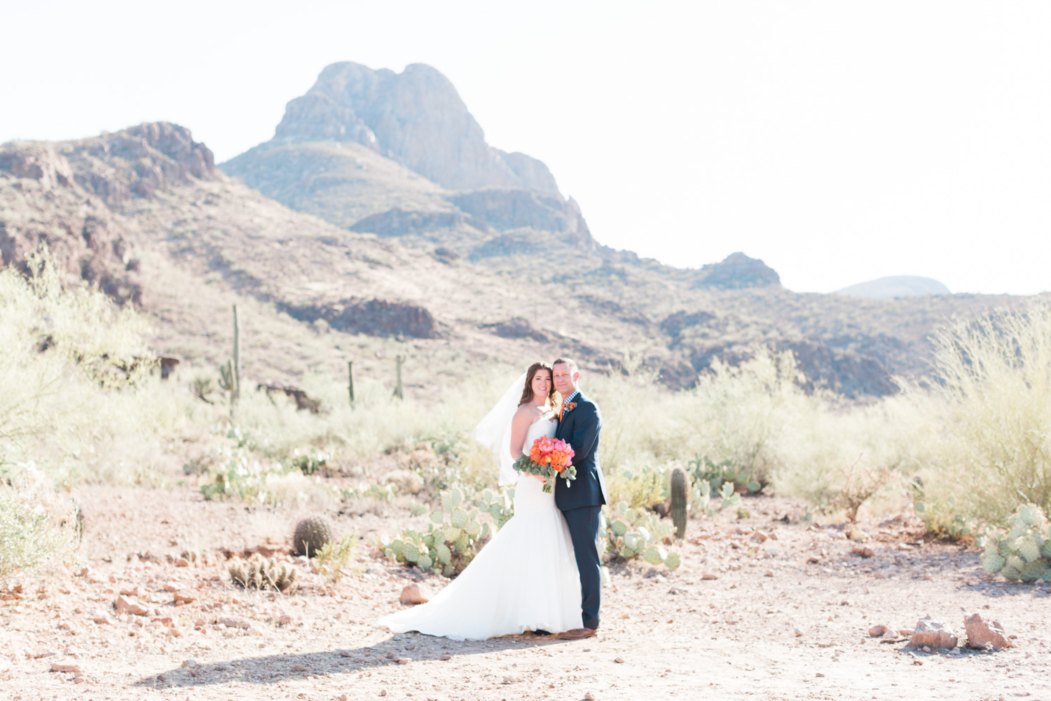 Bride and groom standing in a gorgeous desert setting. Love those stunning mountain views an the cactus in the background! Perfect desert wedding venue.