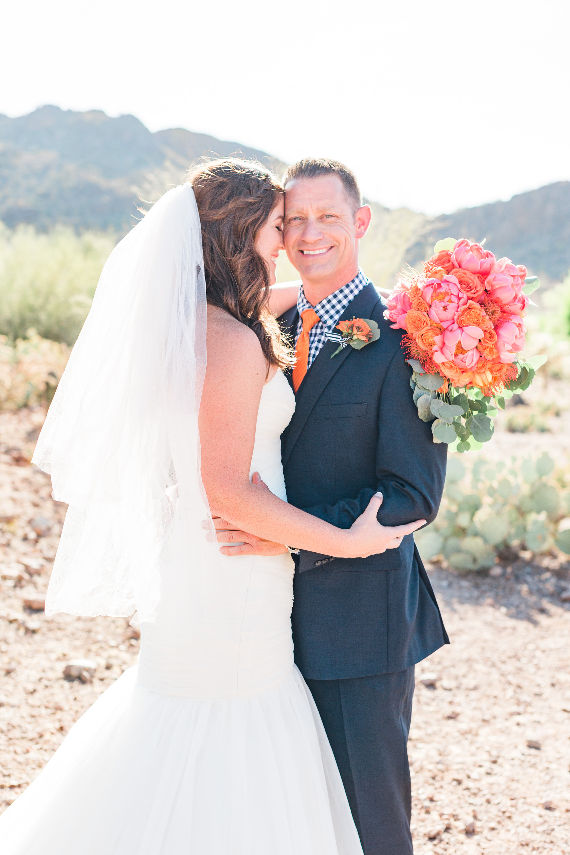Bride hugging her groom, who is smiling at the camera. Love that beautiful desert light shining from behind them!