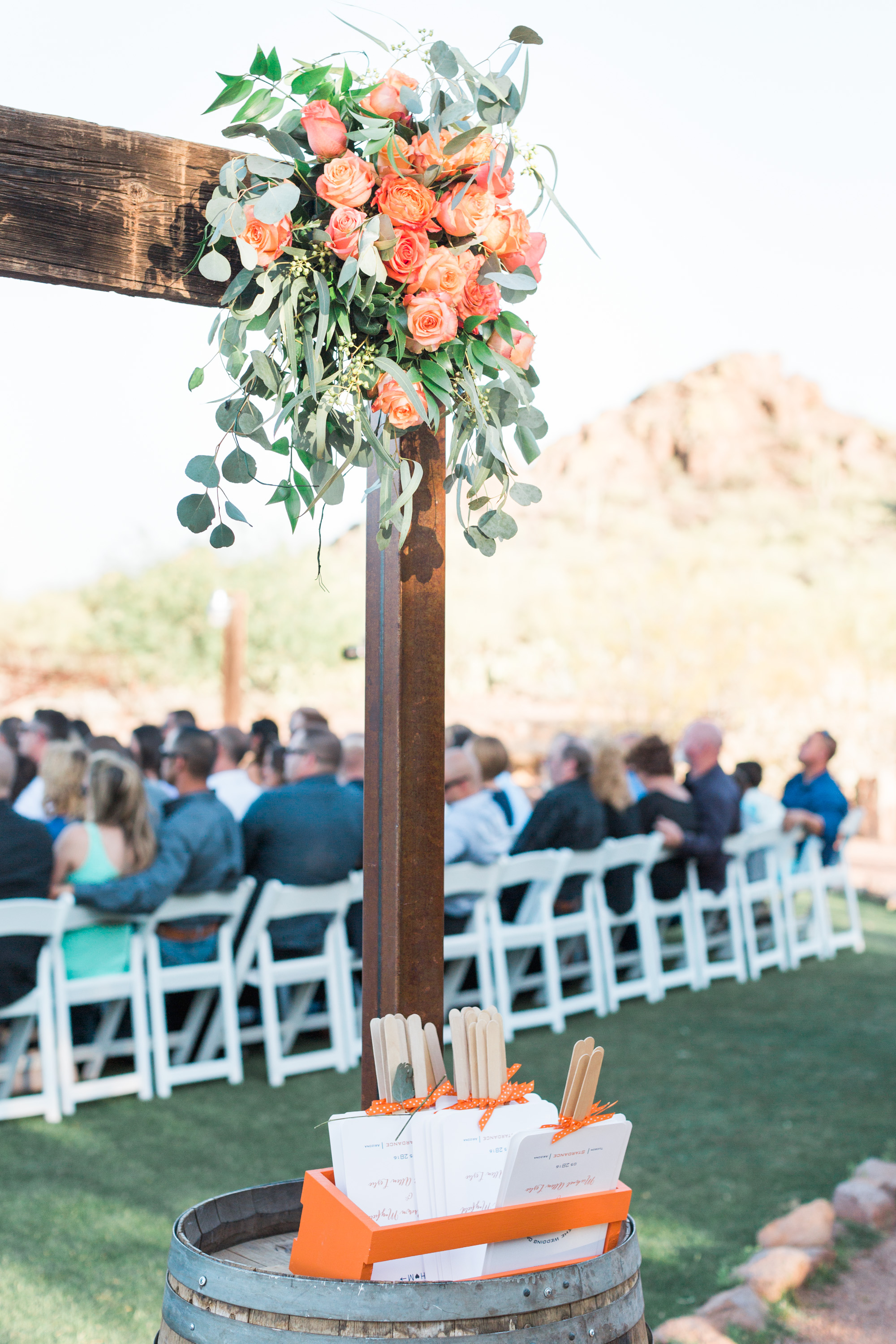 Beautiful arbor at ceremony site with guests in the background.