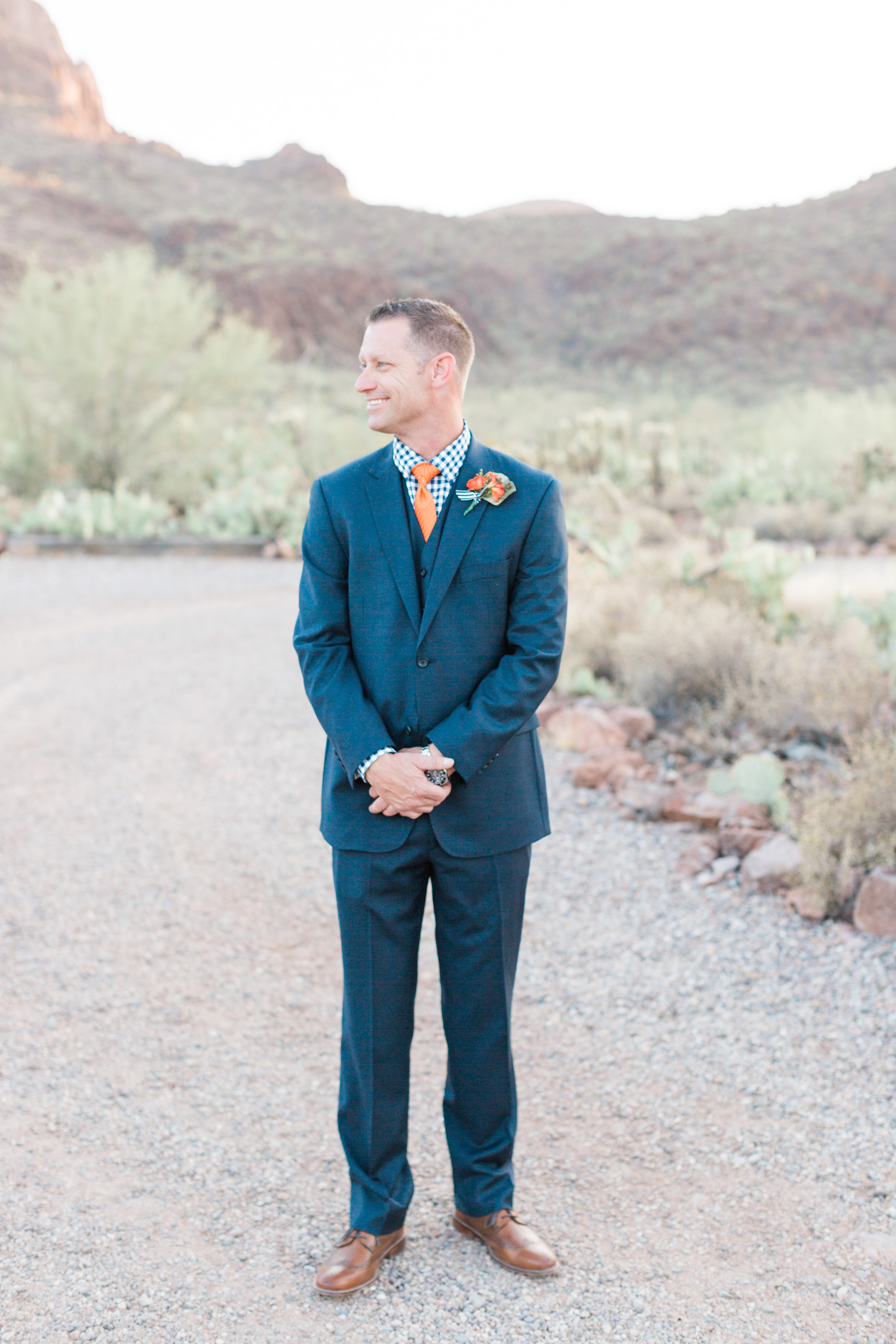 Handsome groom staring at his beautiful bride while she gets her photos taken. Love the way he looks at her!!