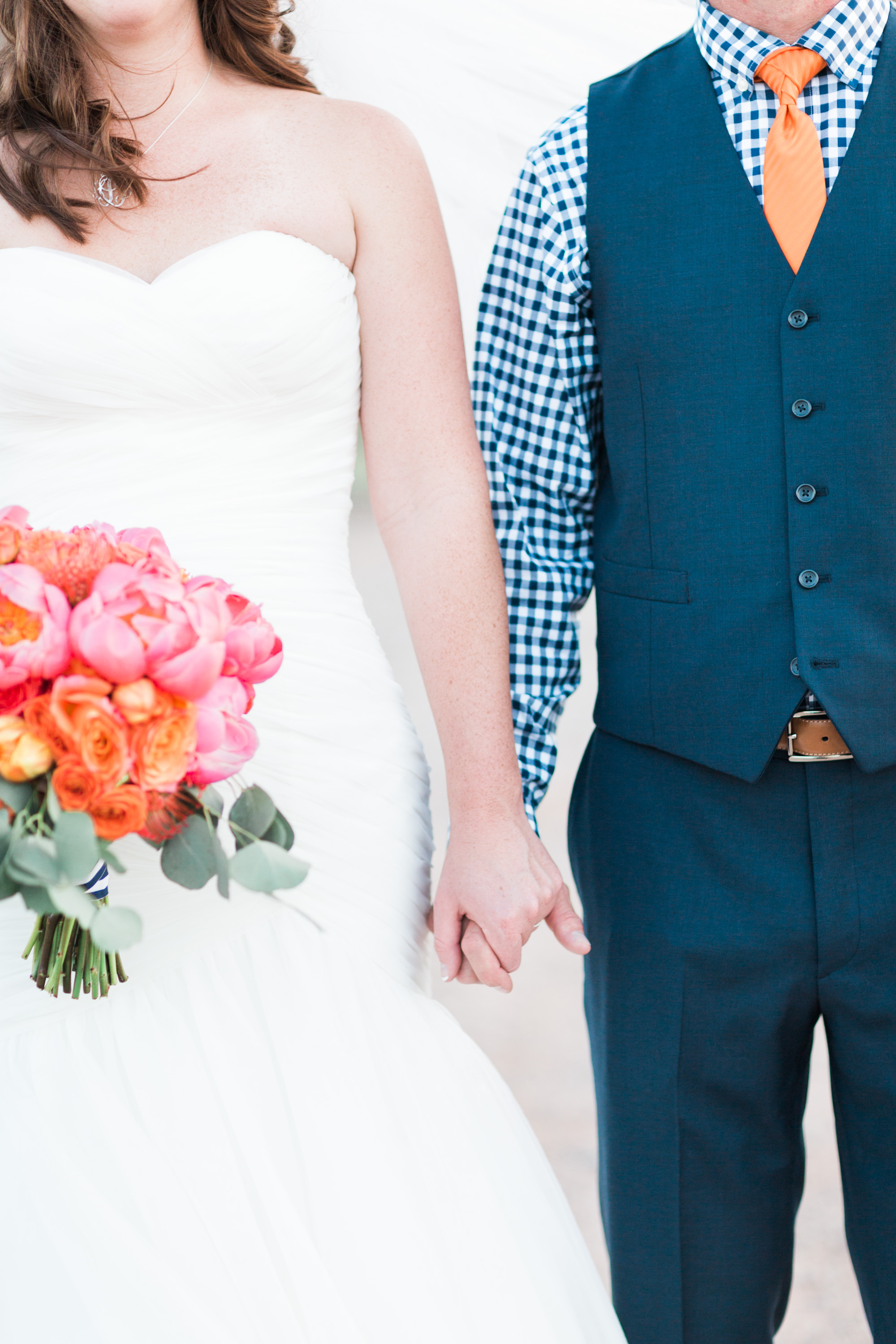 Bride and groom holding hands, standing side by side.