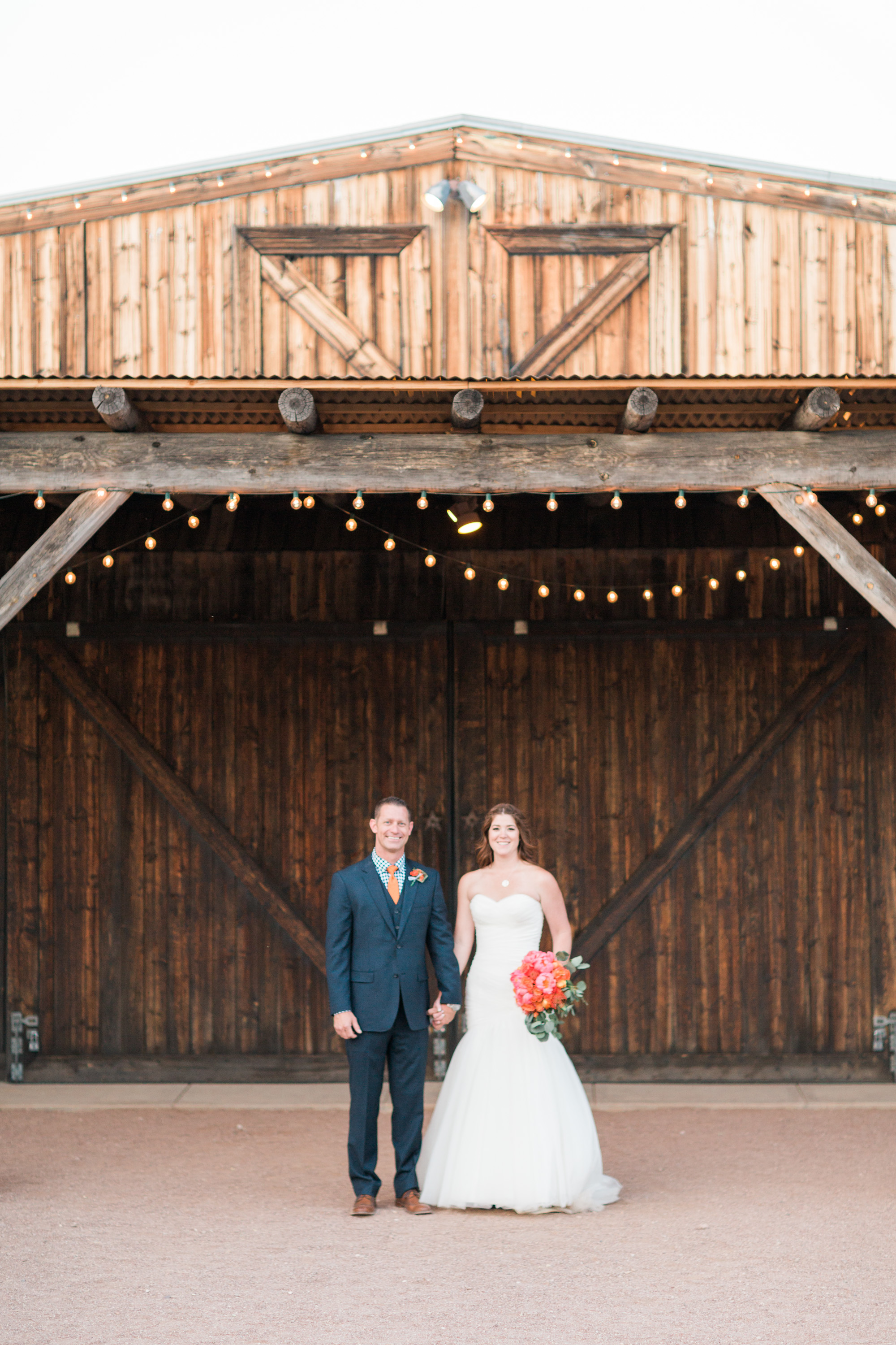 Bride and groom standing in front of the barn doors at Stardance in Tucson.