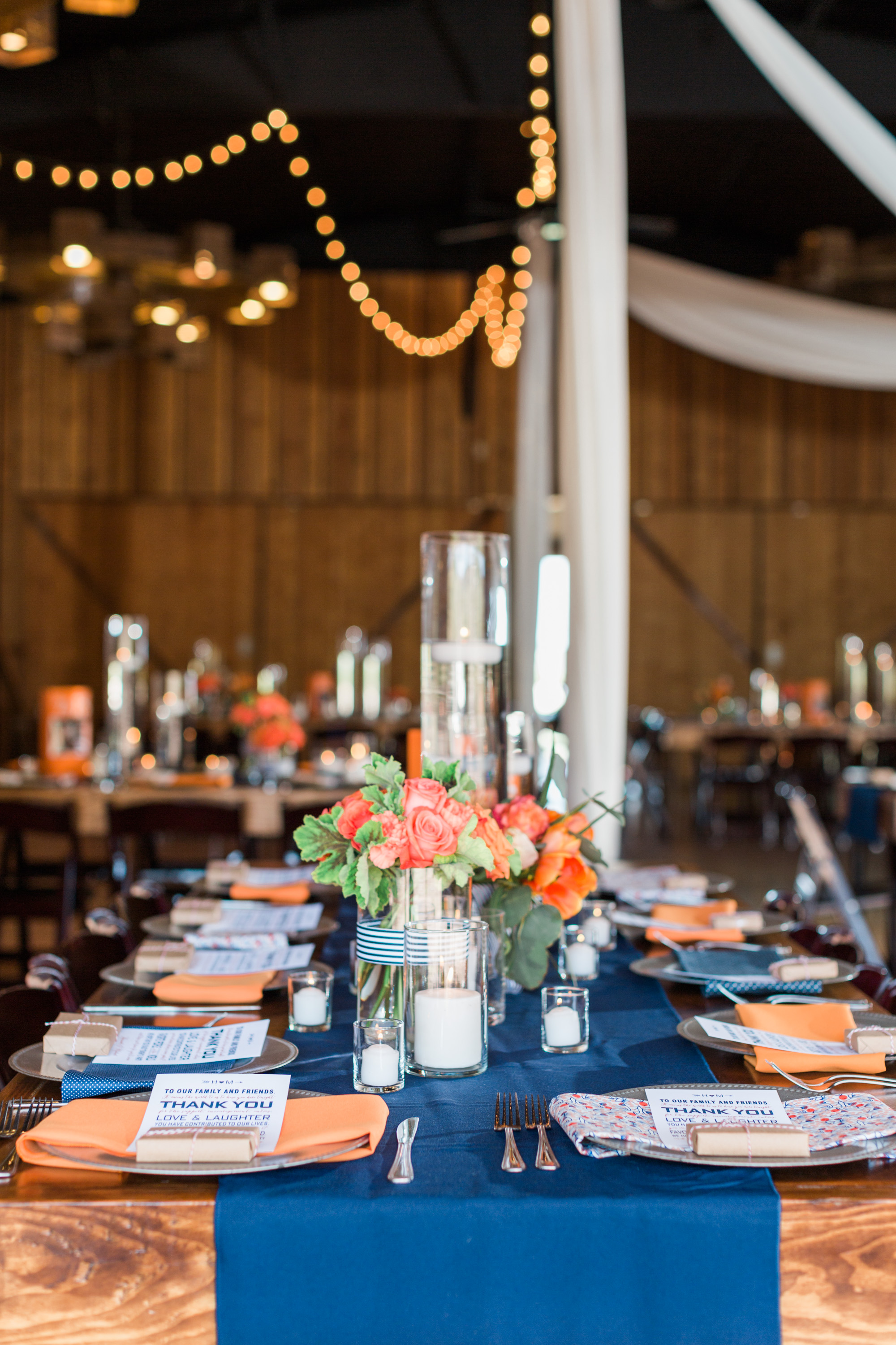Beautiful navy and orange reception set up at Tucson barn wedding venue, Stardance.
