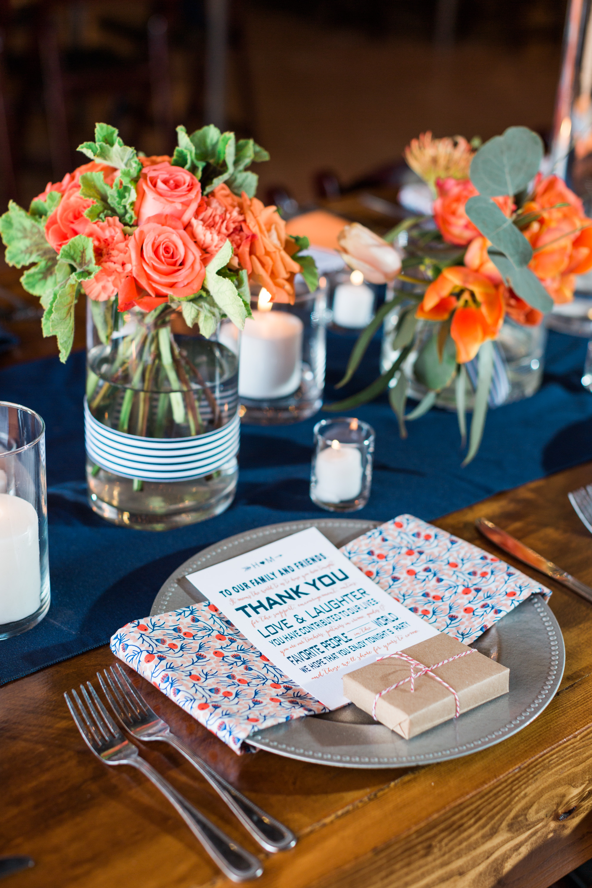 Love the orange and navy color scheme of this wedding reception! Candles everywhere and a super cute thank you on each plate.