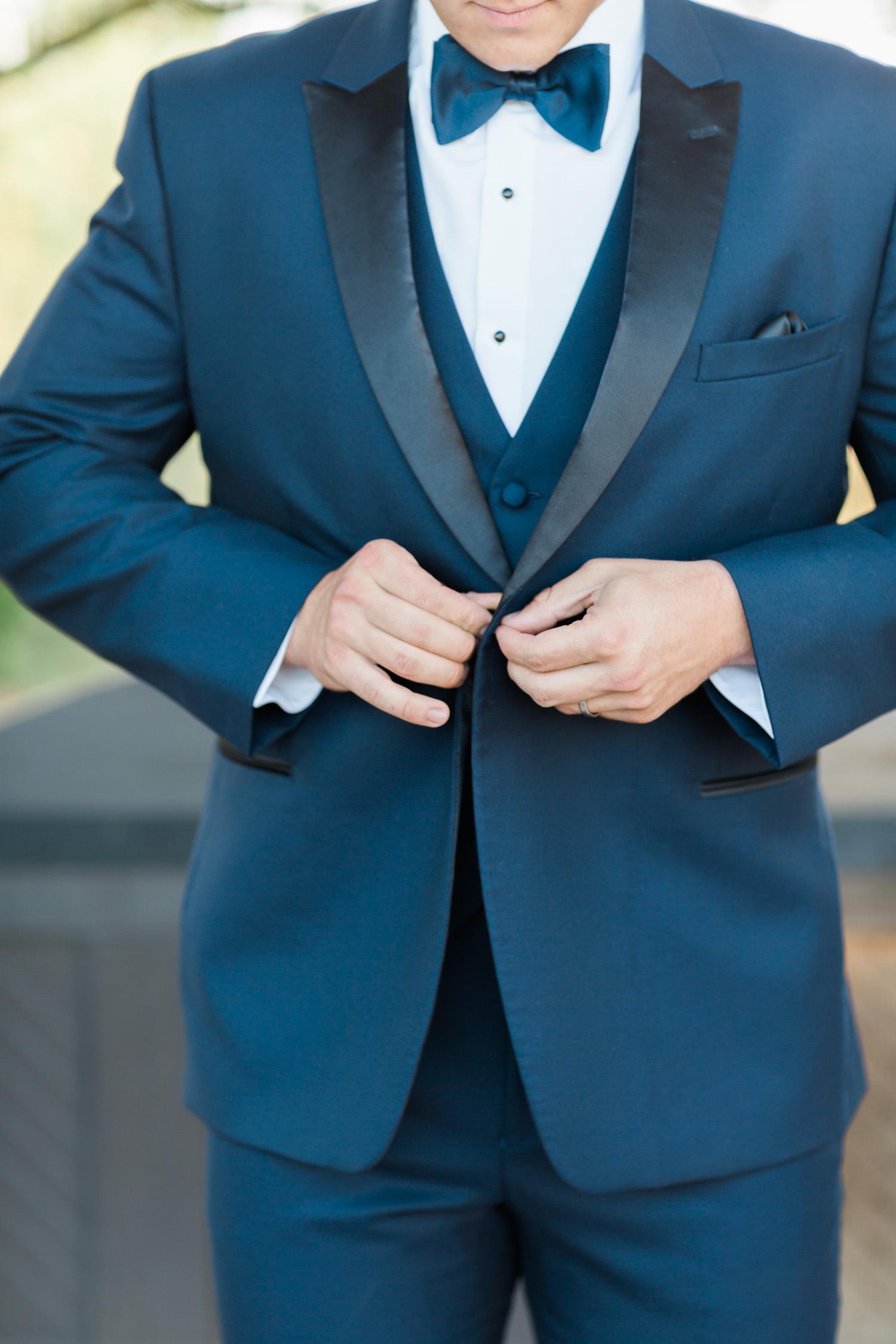 Groom in navy, buttoning hus tuxedo jacket