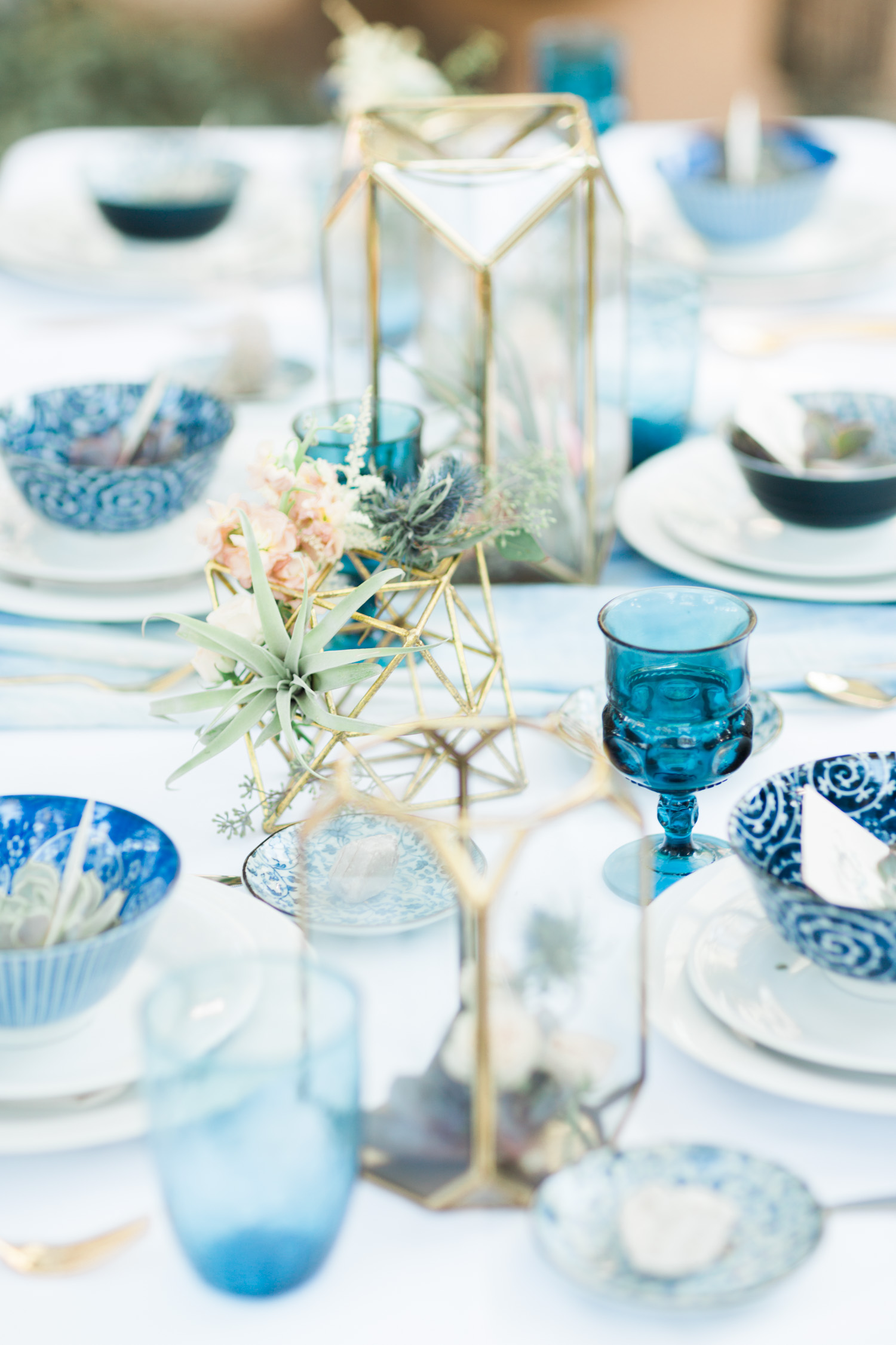 Indigo and gold tablescape with hints of blush florals and air plants