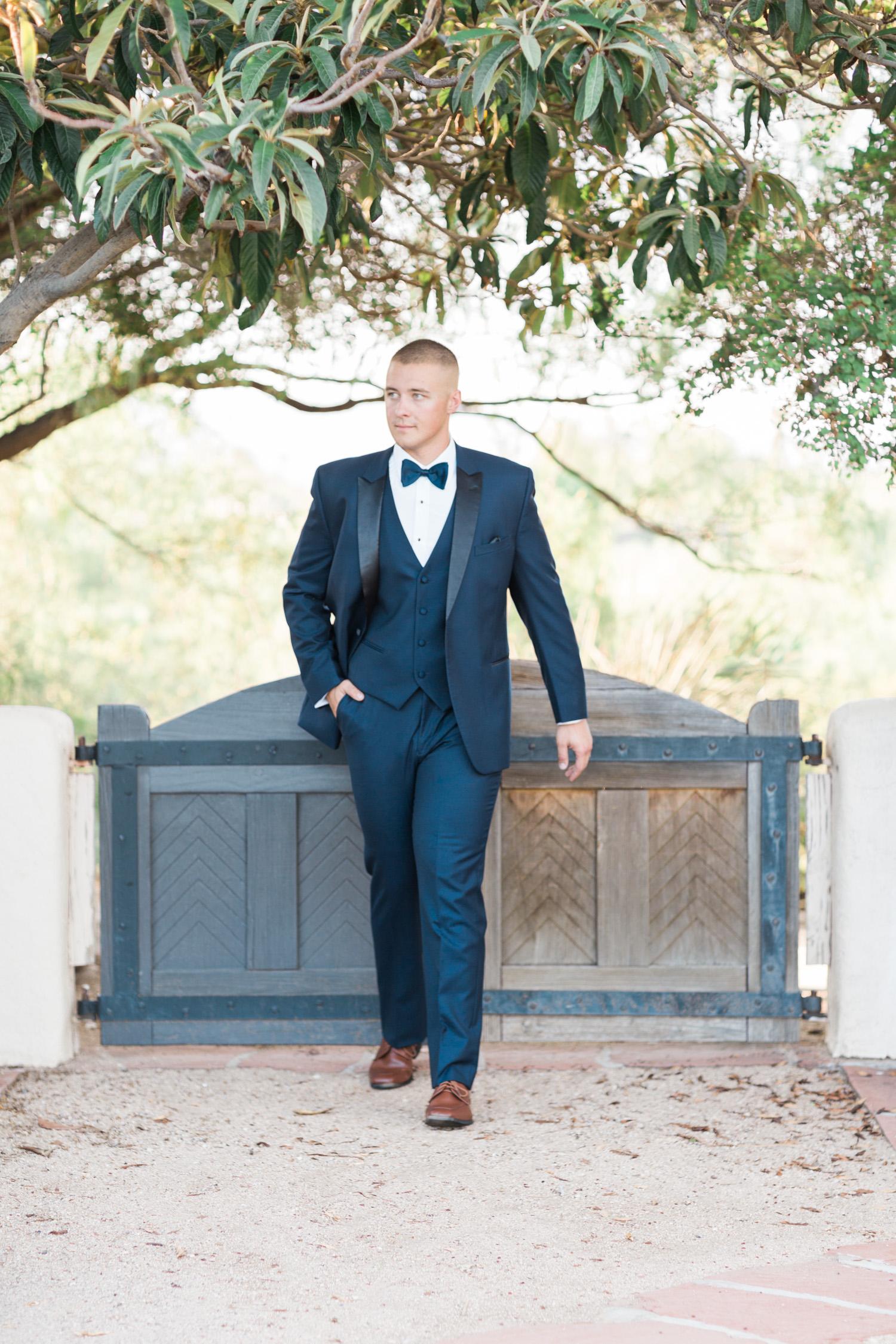 Handsome groom in a navy tux walking