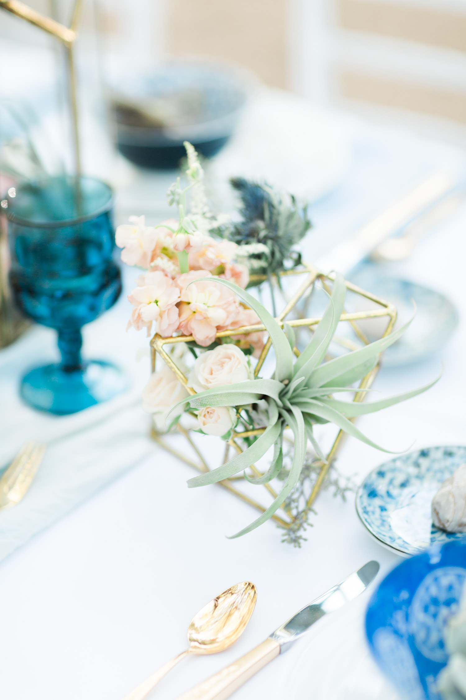 Gold and indigo table setting with air plants and gold flatware