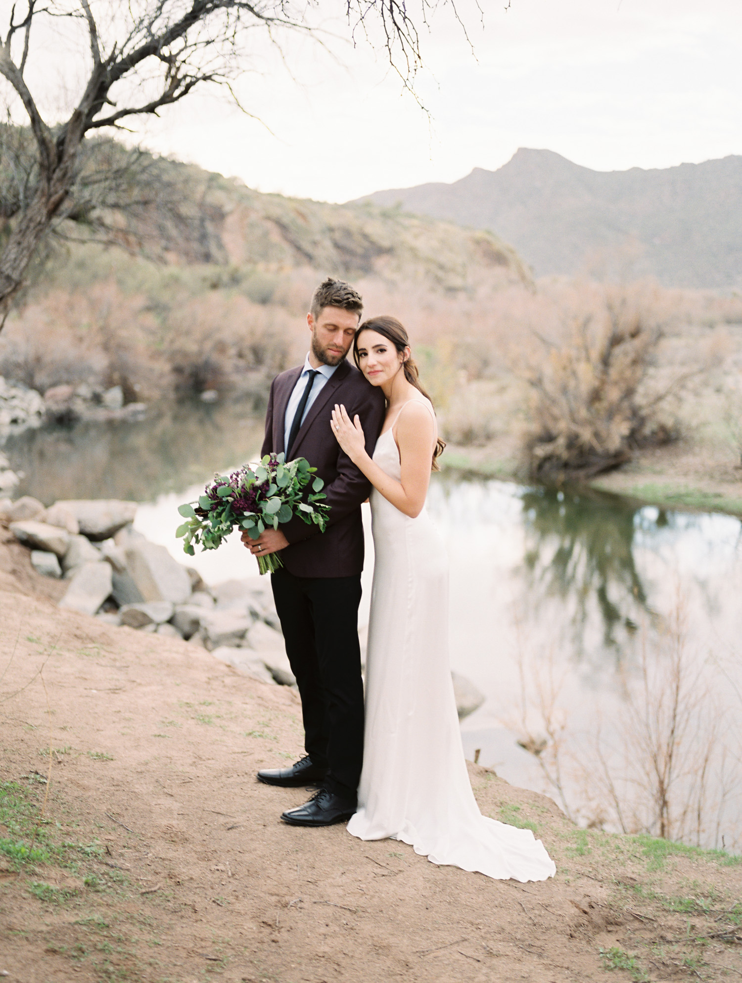 Gorgeous bride embracing her groom who is holding her bouquet. Gorgeous salt river views in the background.
