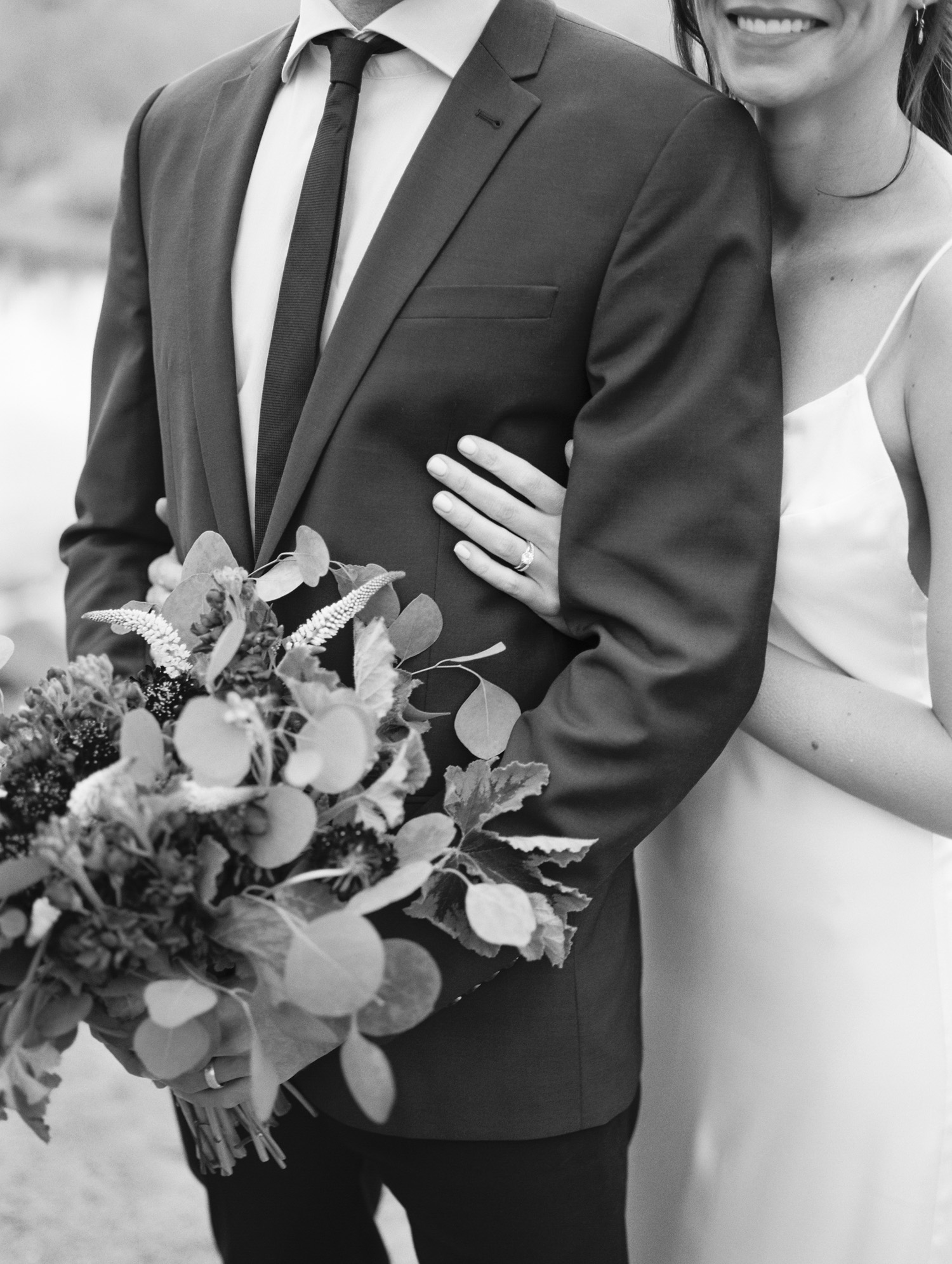 Black and white photo of groom holding bouquet and bride smiling and hugging her groom.