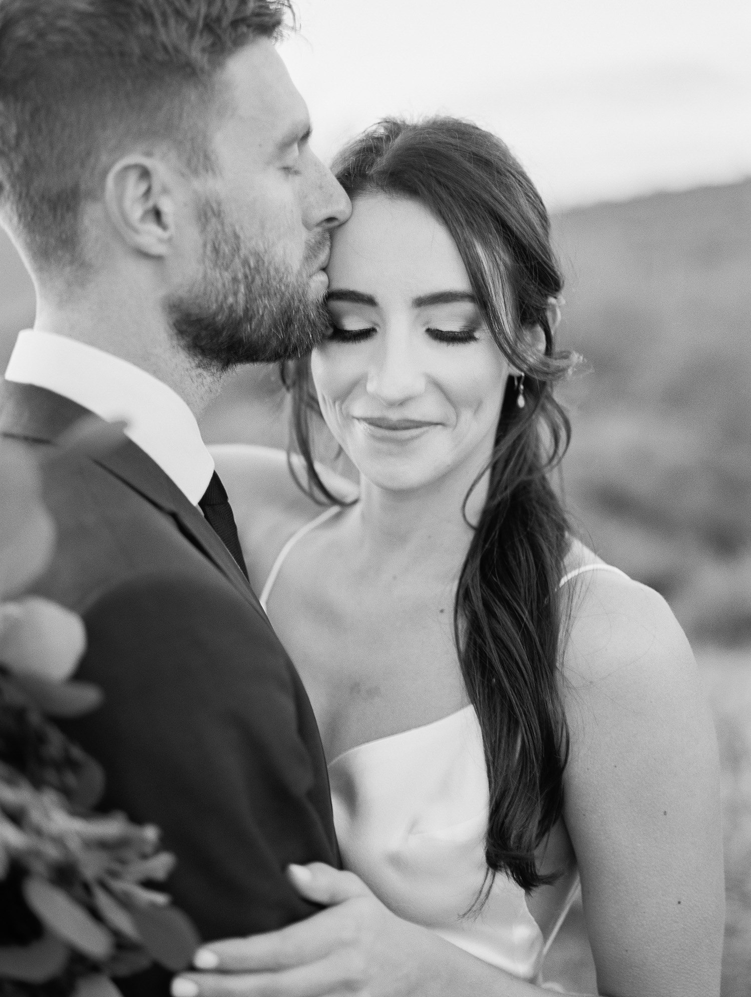 Such a sweet photo of groom kissing his new bride on the forehead at their Phoenix elopement.