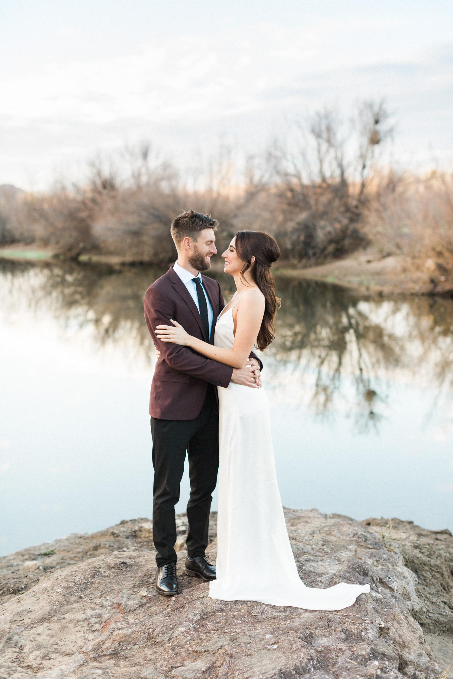 Beautiful bride and groom embracing at their Phoenix elopement with the Salt River in the background.