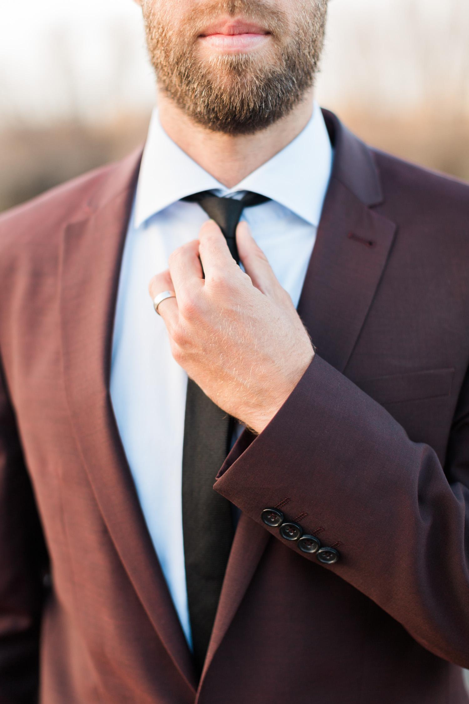Straightening his tie, wearing a classy burgundy jacket.