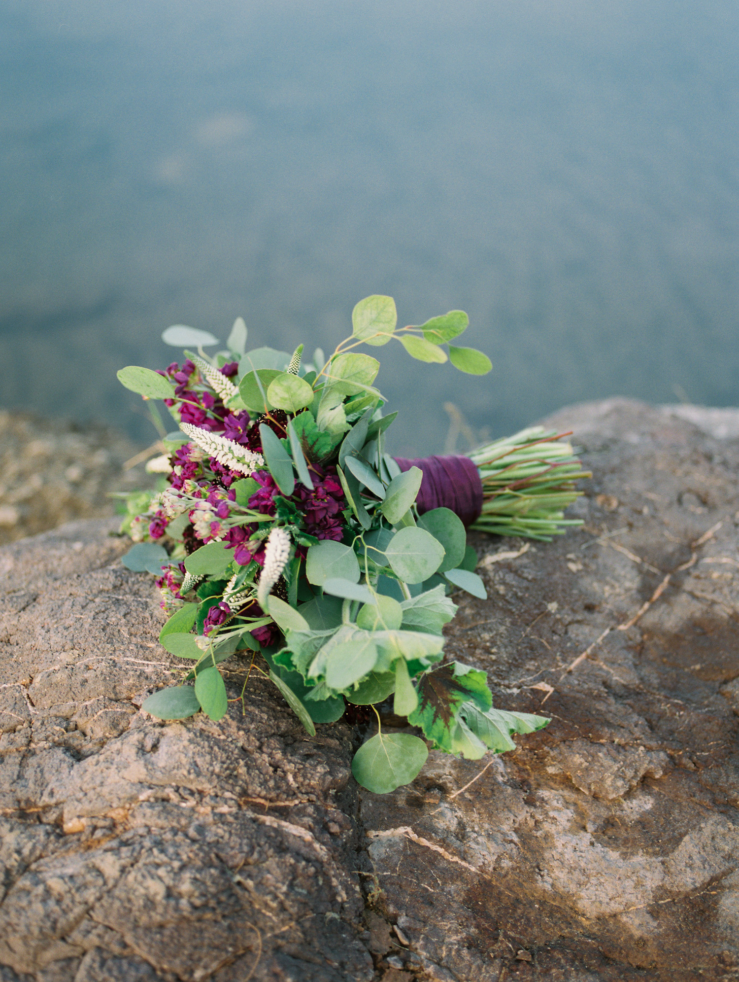 Stunning burgundy, purple bouquet by Phoenix florist, Butterfly Petals laying on a rock along the banks of the Salt River.