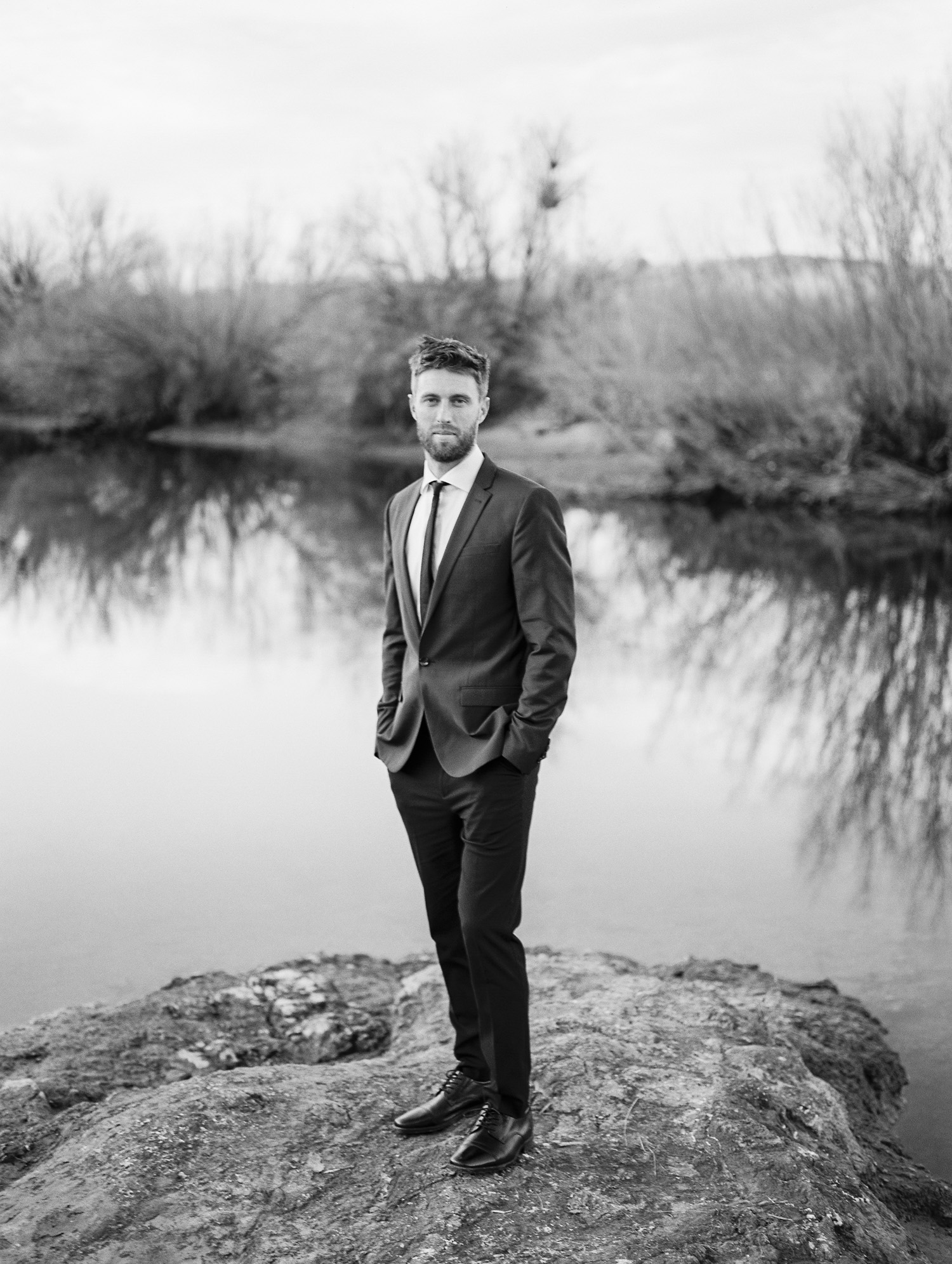Black and white film photo of groom along the Salt River in Phoenix, AZ.