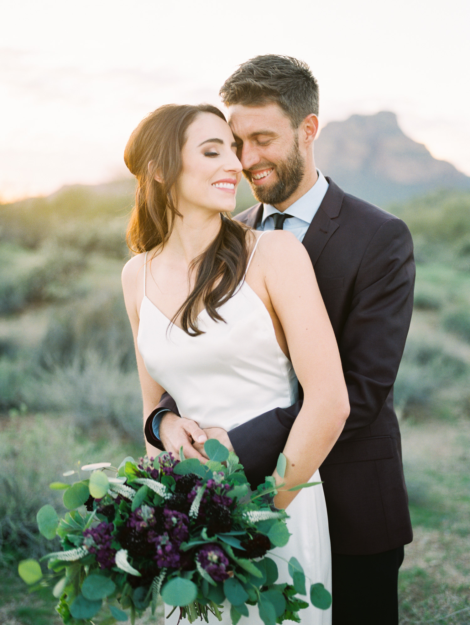 Couple embracing on their wedding day with amazing desert views in the background.