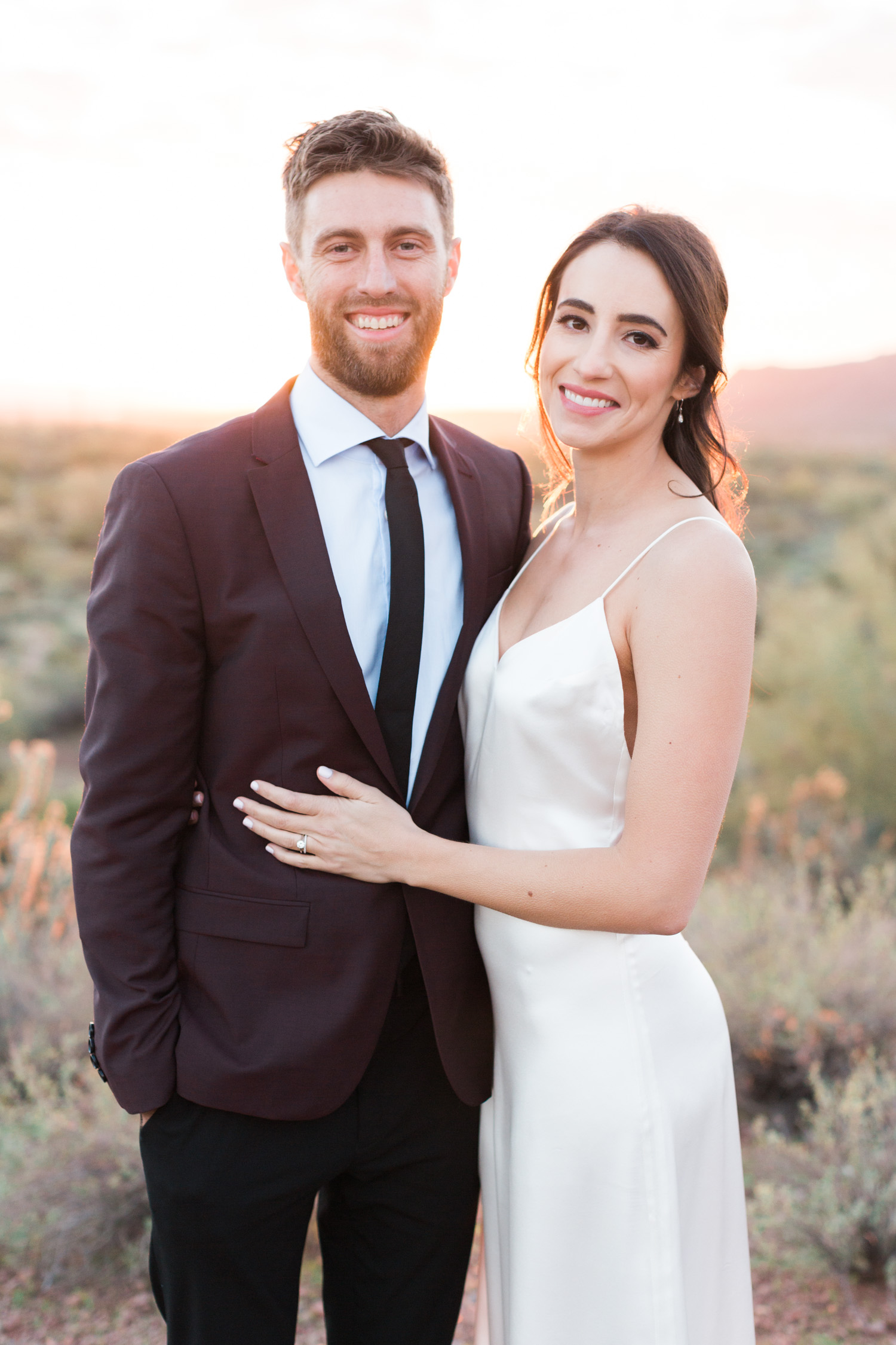 Bride and groom smiling at the camera with a gorgeous Phoenix sunset on their wedding day!