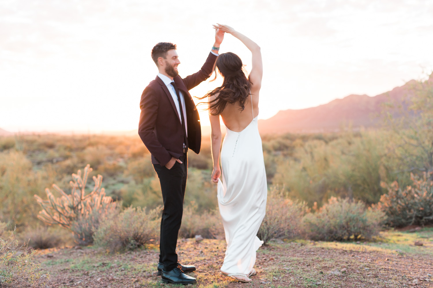 Groom twirling his bride in the desert on their wedding day.