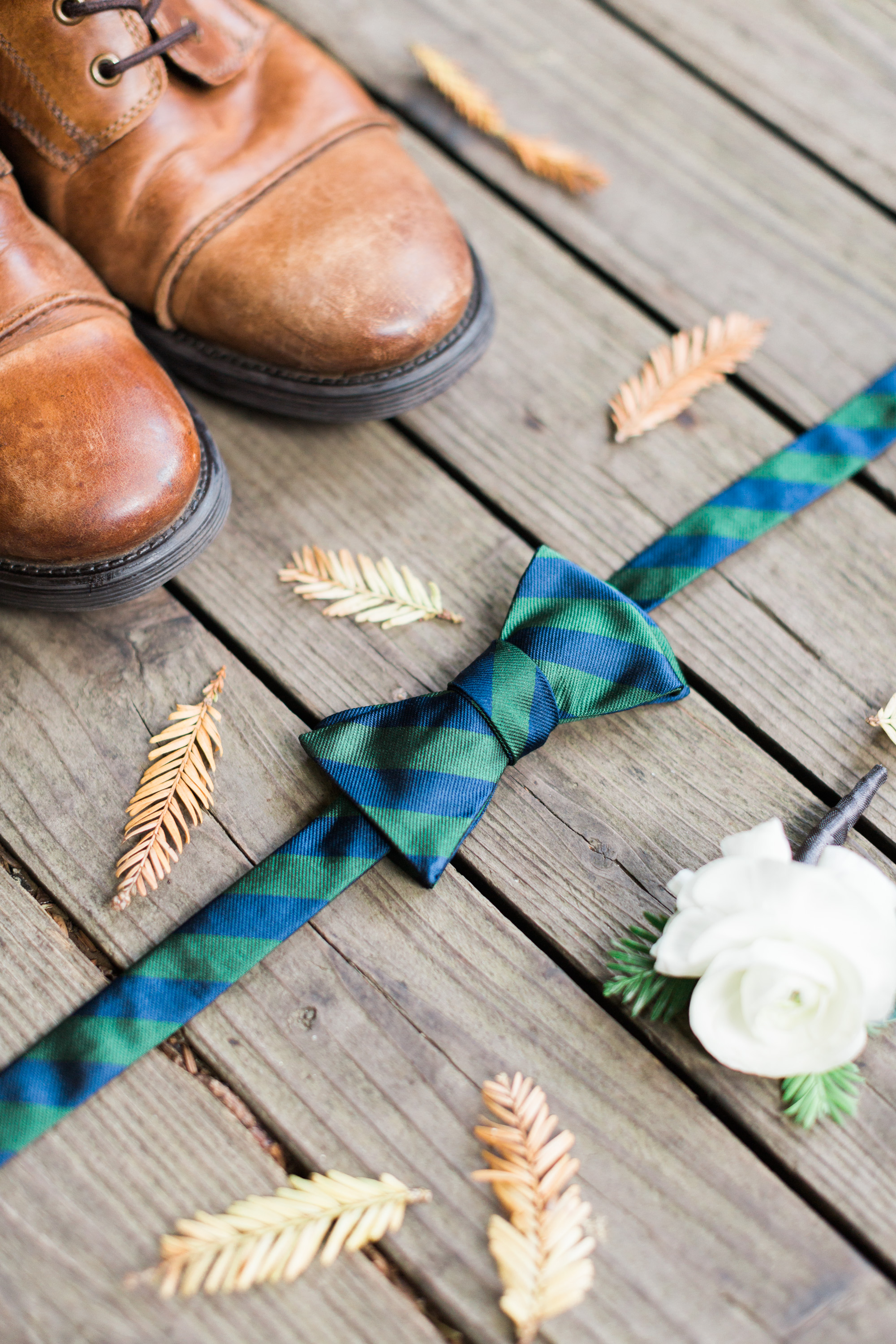 Grooms details with blue bowtie and leather shoes