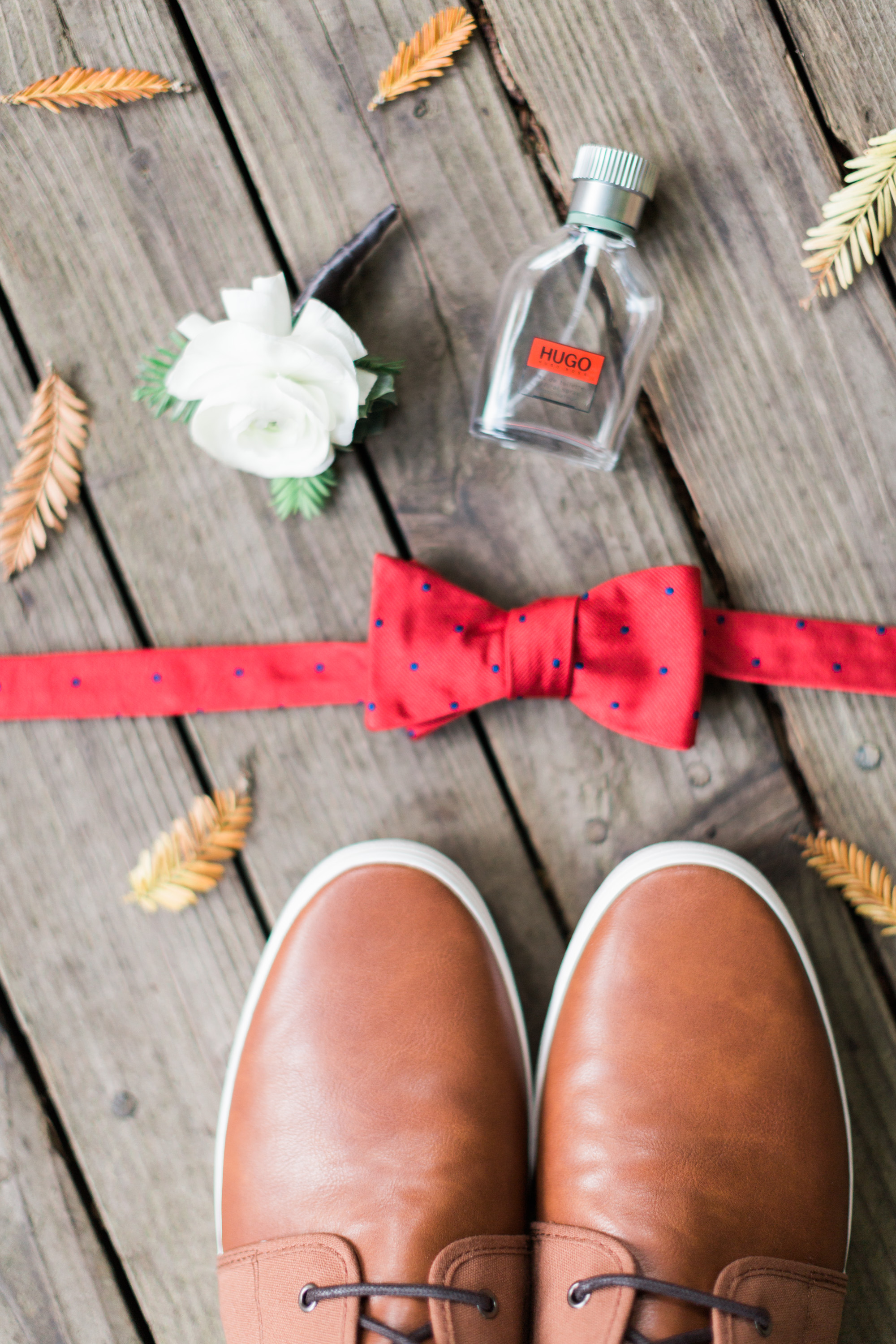 Grooms details with red bowtie, leather shoes, cologne & boutonniere
