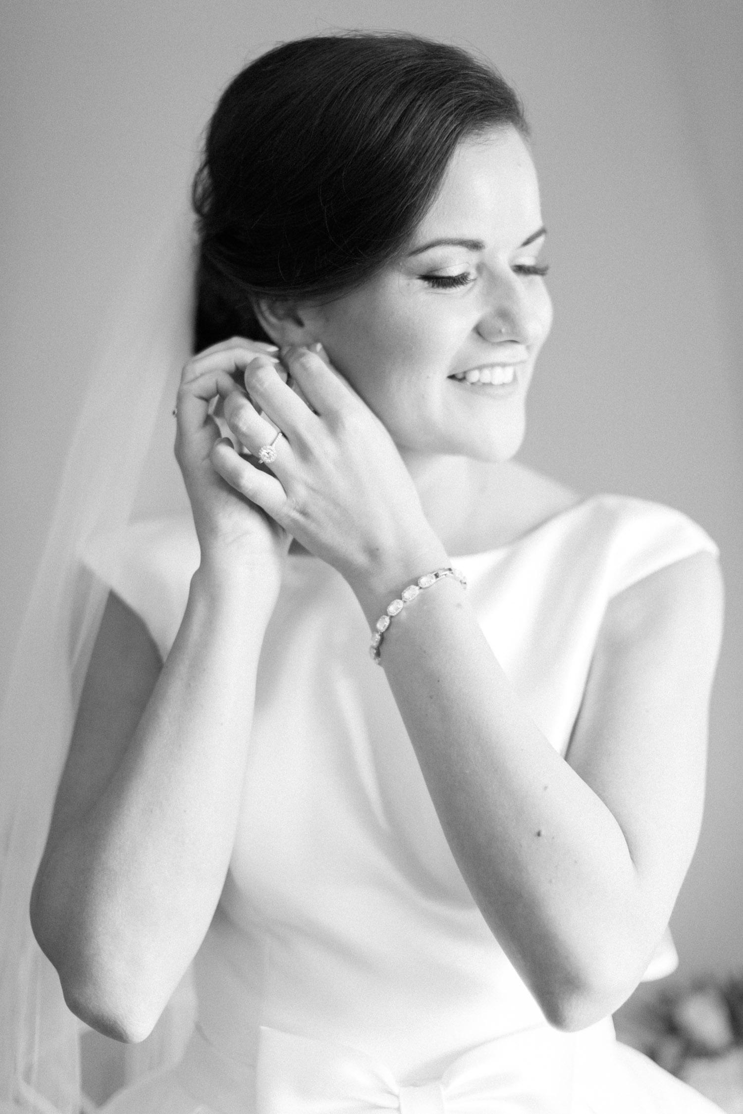 Bride putting on jewelry