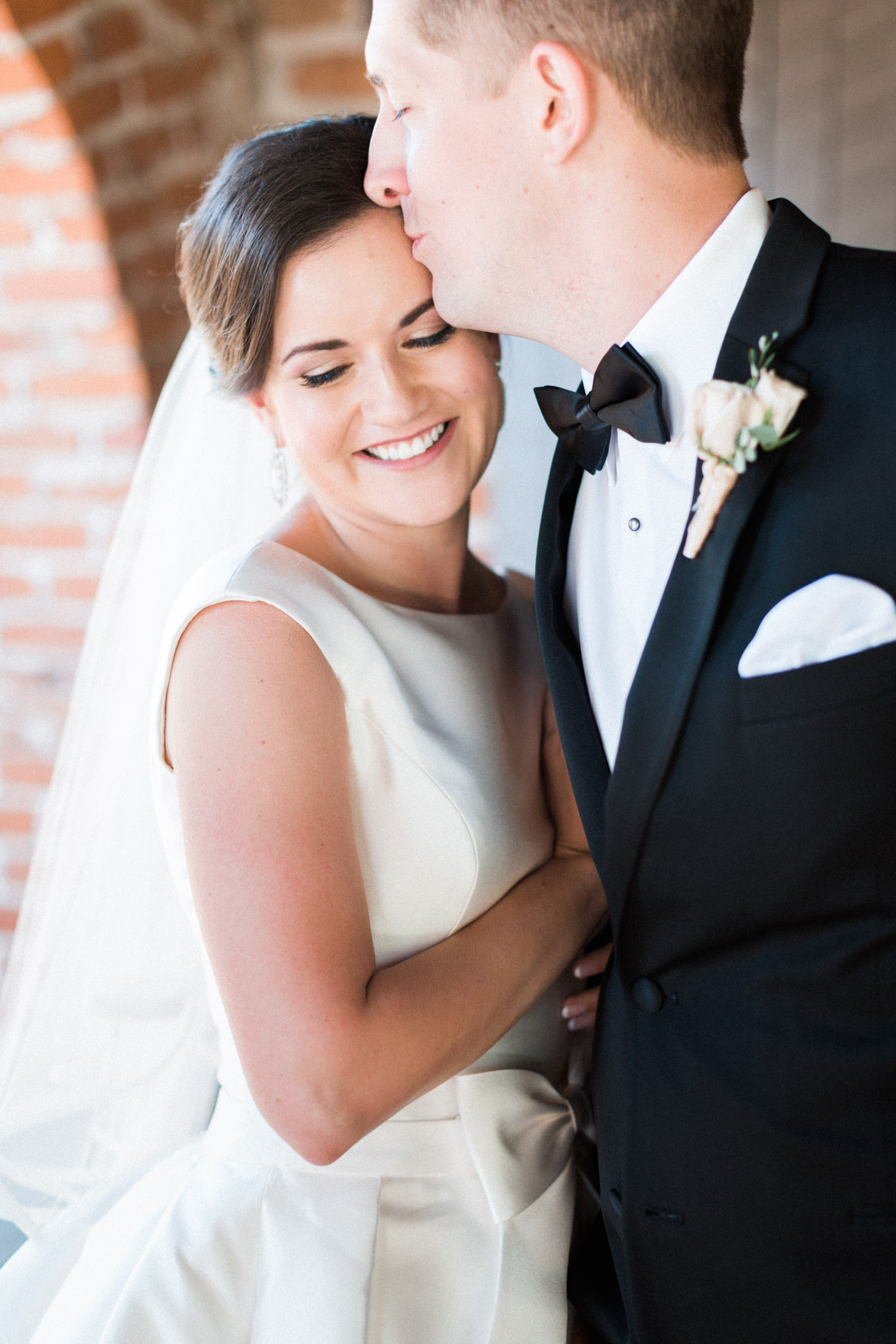 Bride smiling as groom kisses her on the forehead | Betsy & John Photography | Tucson Wedding Photographers