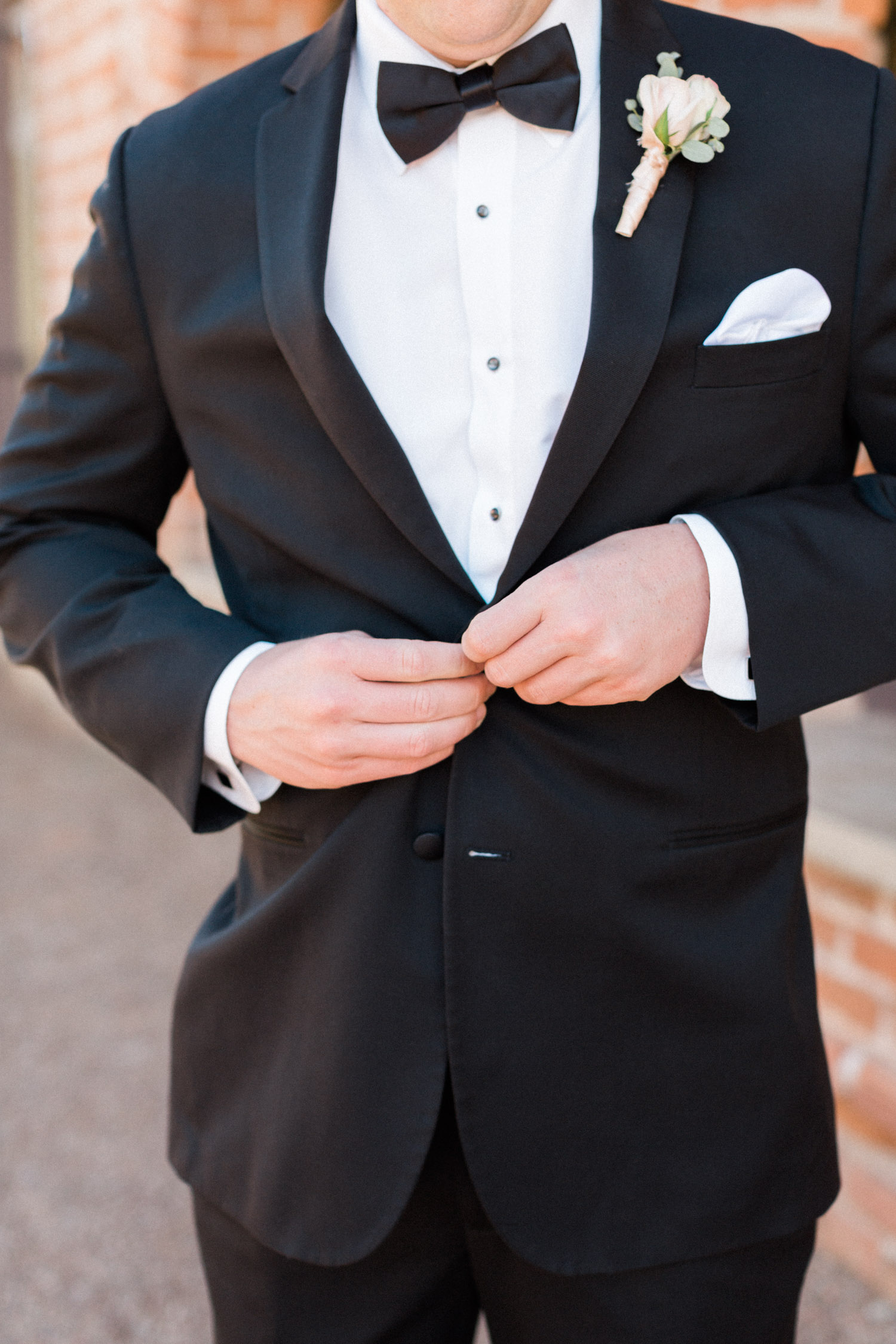 Groom buttoning up black tuxedo