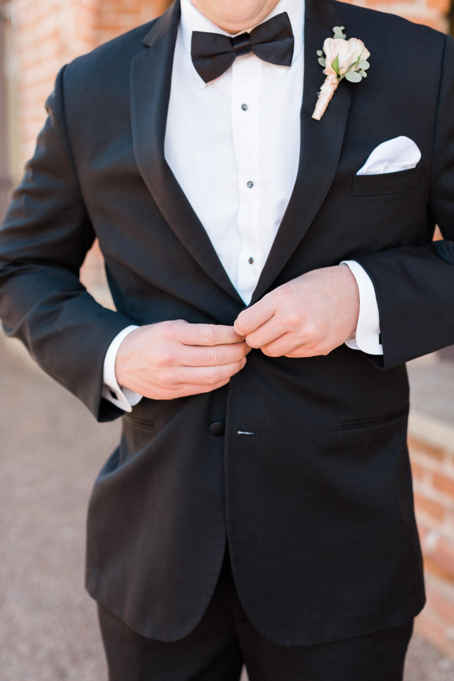 Groom buttoning up black tuxedo