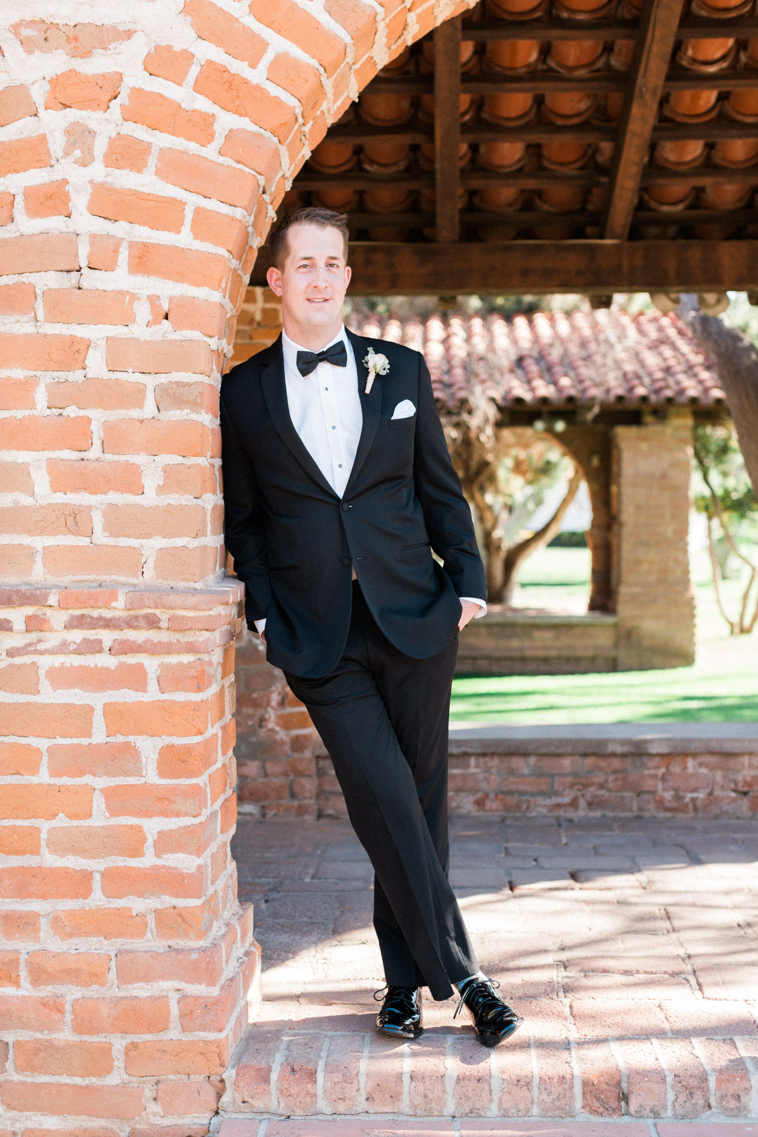Groom leaning against wall