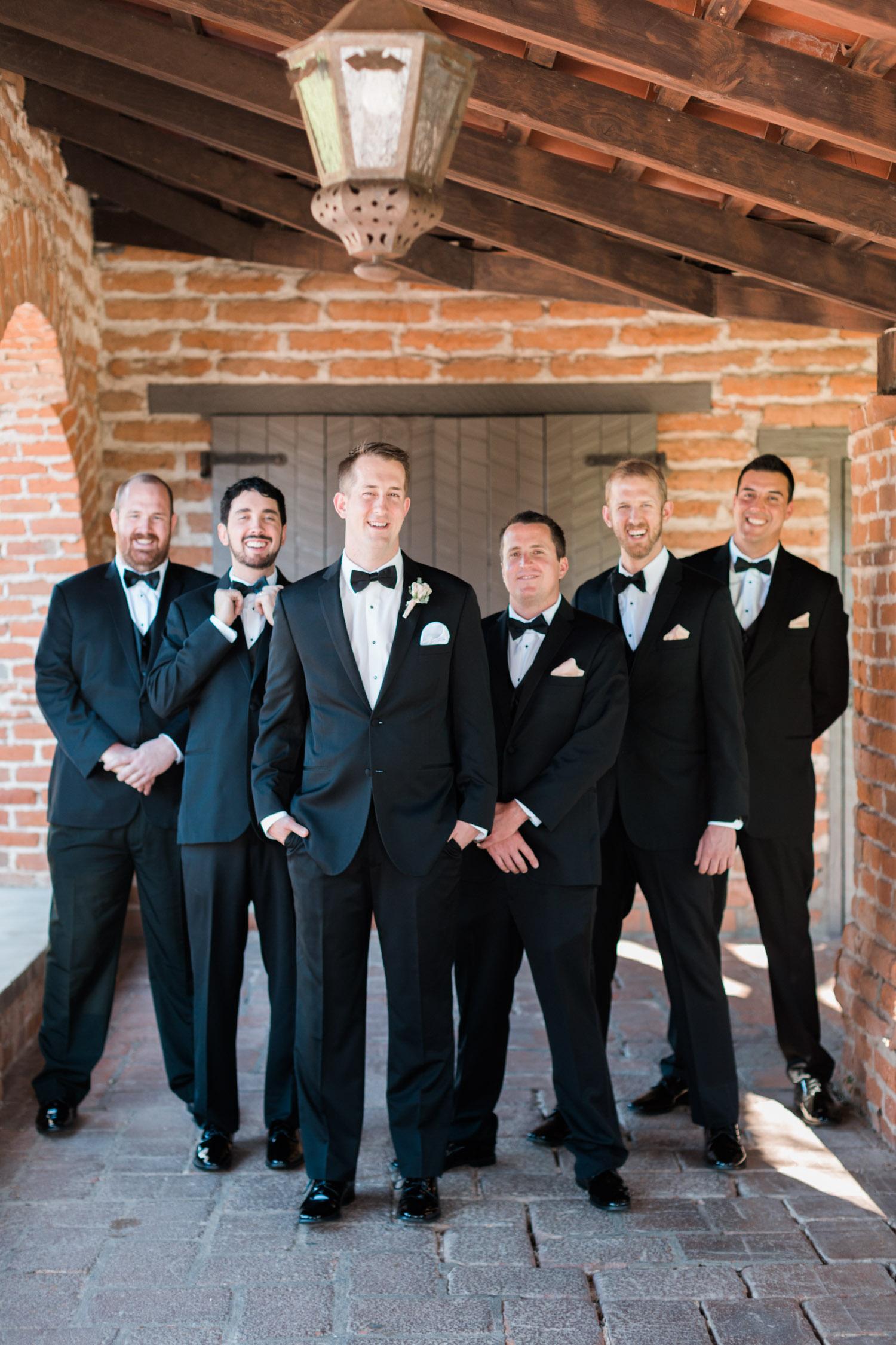 Groom with groomsmen in black tuxedos