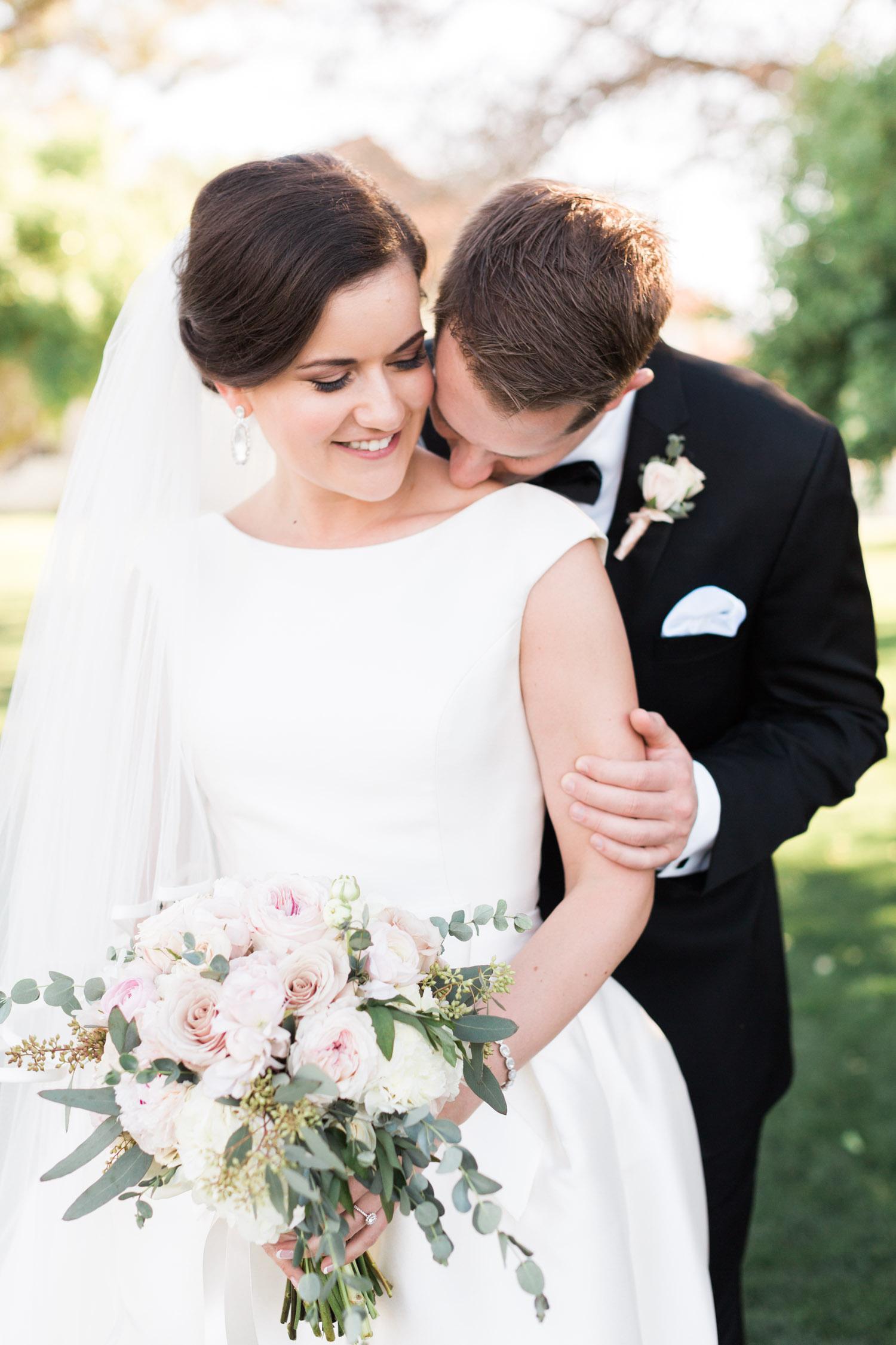 Groom kissing bride on shoulder| Betsy & John Photography | Tucson Wedding Photographers