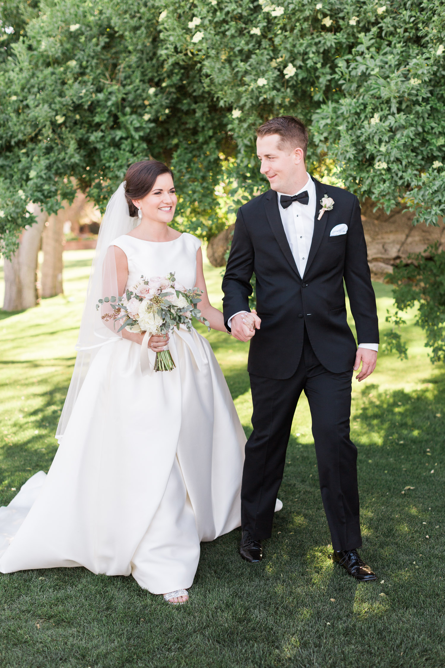 Bride and groom walking at their Tubac Golf Resort wedding. Gorgeous green Arizona wedding venue.  | Betsy & John Photography | Tucson Wedding Photographers