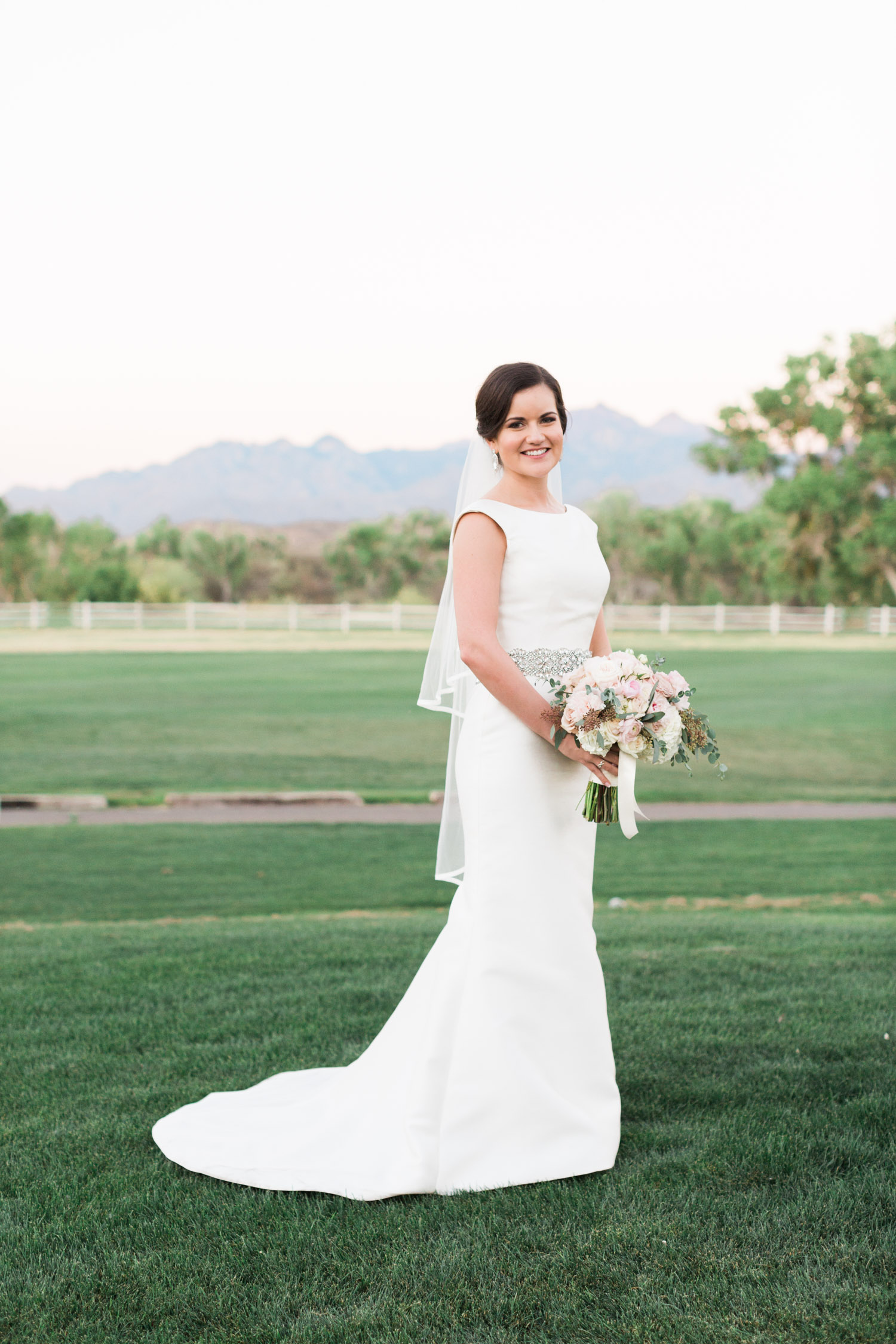Bride wearing a fitted Pronovias gown, holding flowers with mountain views in the background