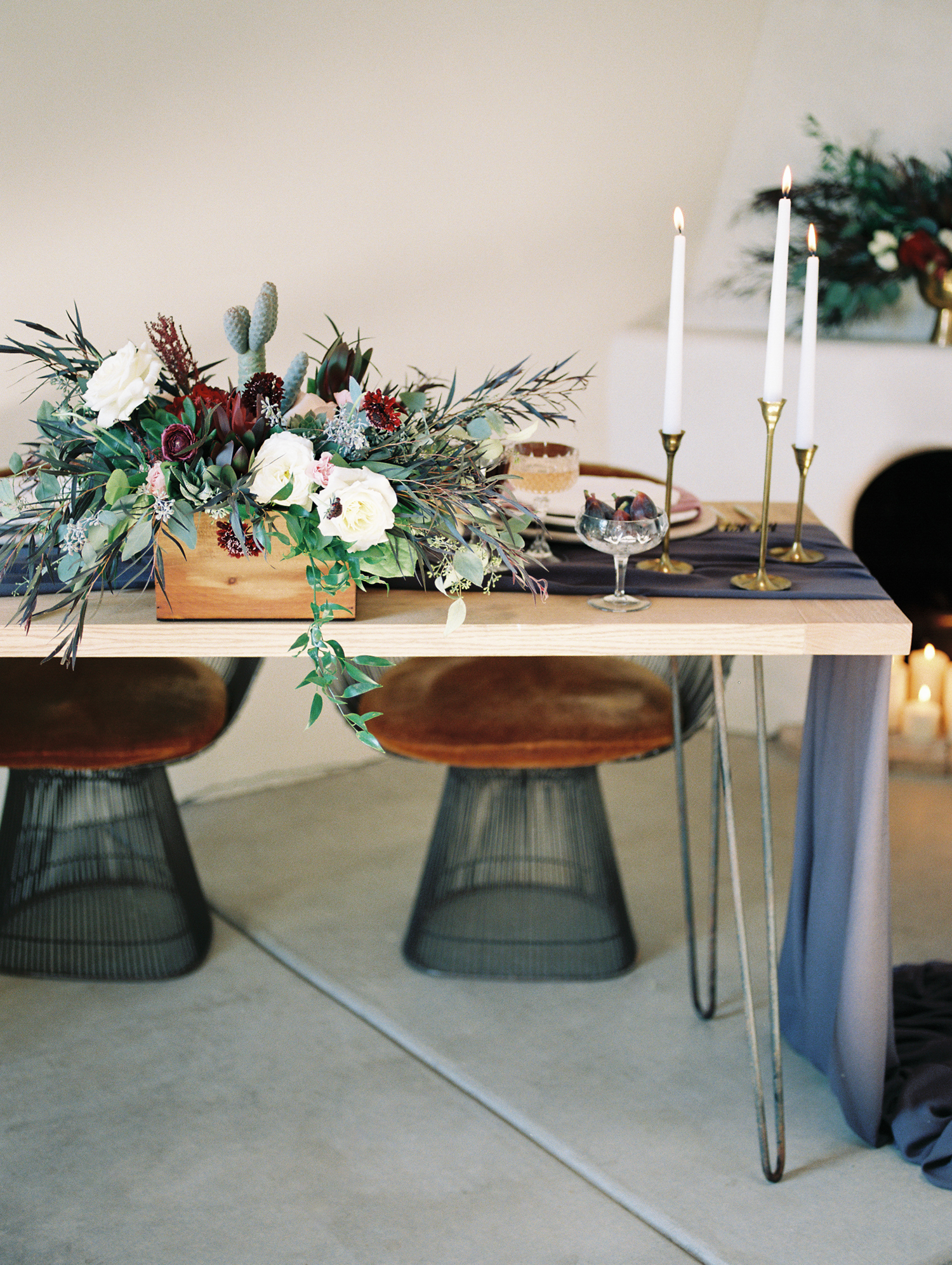 Hipster wedding reception set up with wild florals and tall candles in brass candlesticks