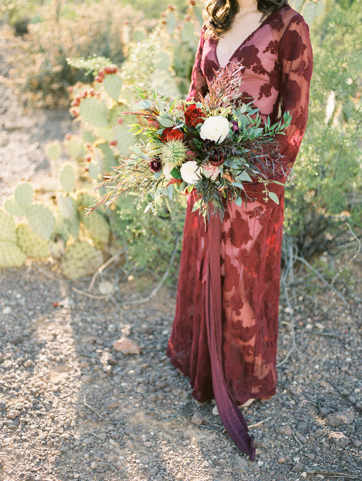 Stunning burgundy lace wedding dress paired with a fall desert bridal bouquet with cactus
