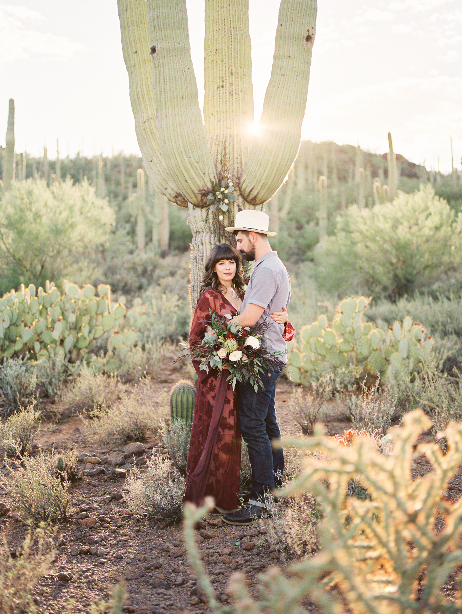 hip couple standing in front of a saguaro