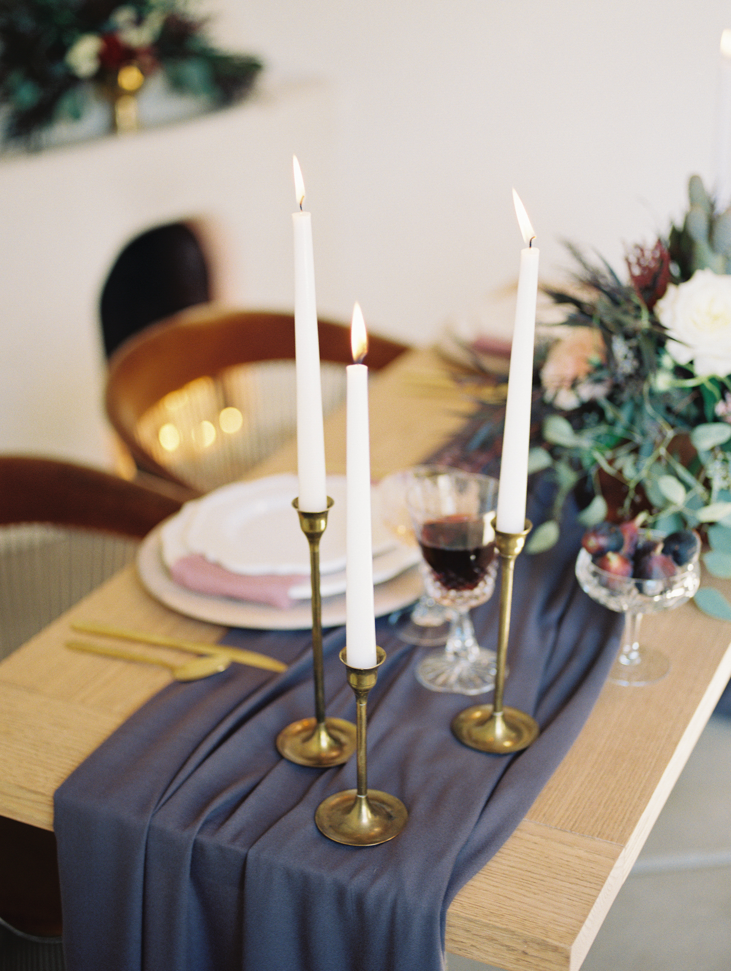 table setting with tall white tapered candles in brass candlesticks and a plum table runner