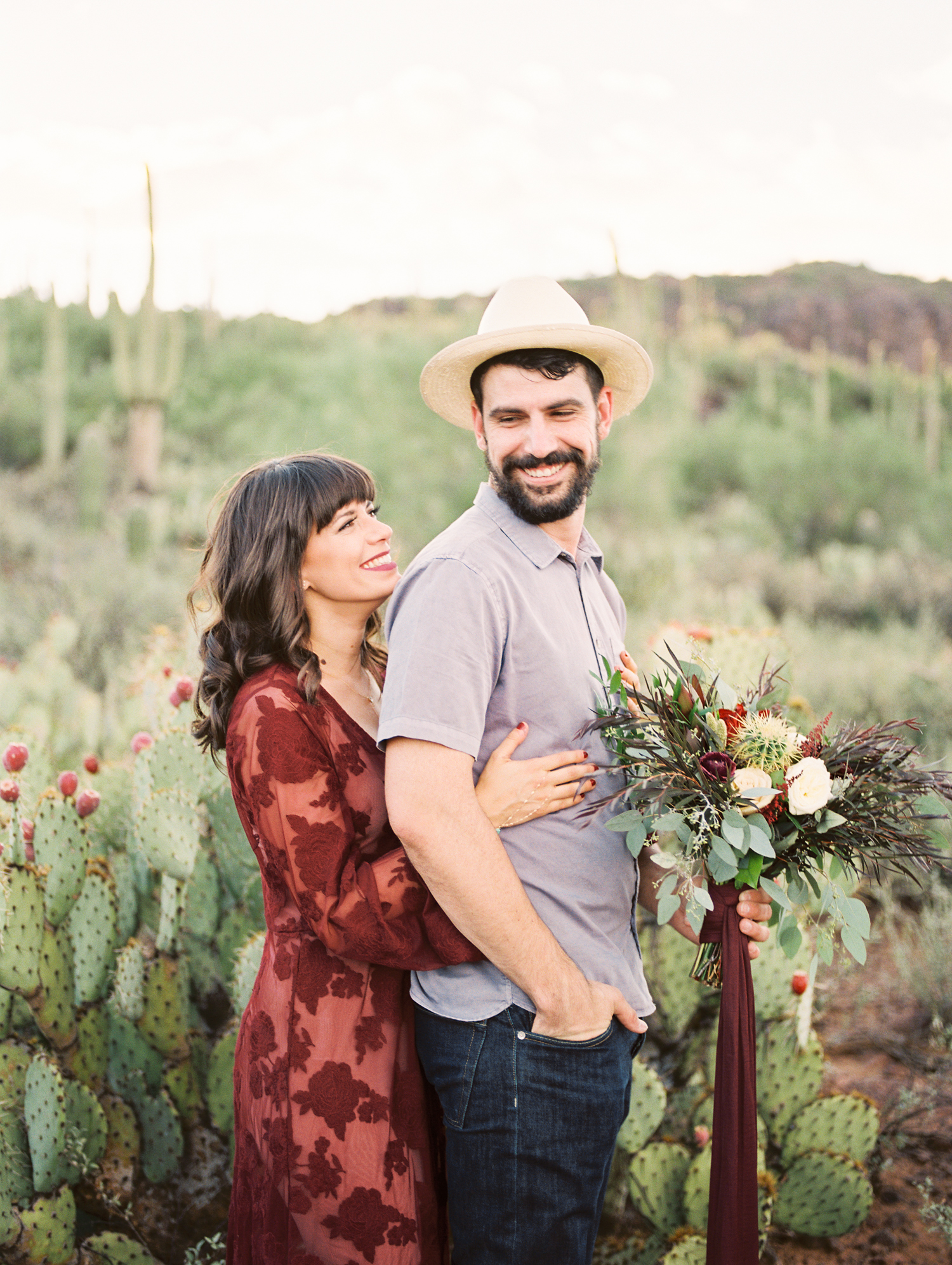 Couple smiling at each other with cactus in the background. Tucson wedding