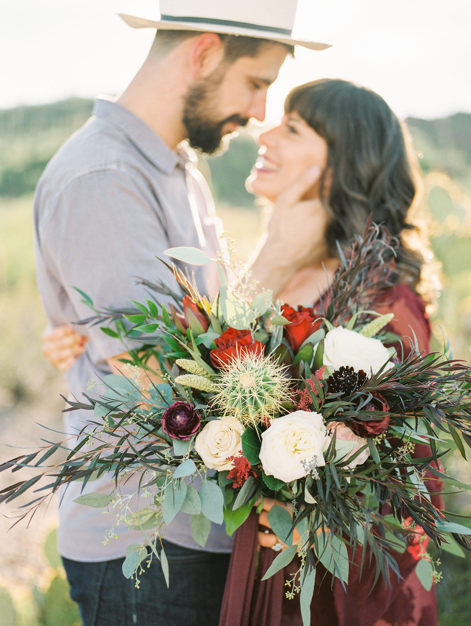 Couple smiling at each other with gorgeous desert backlighting on film and bridal bouquet in the foreground
