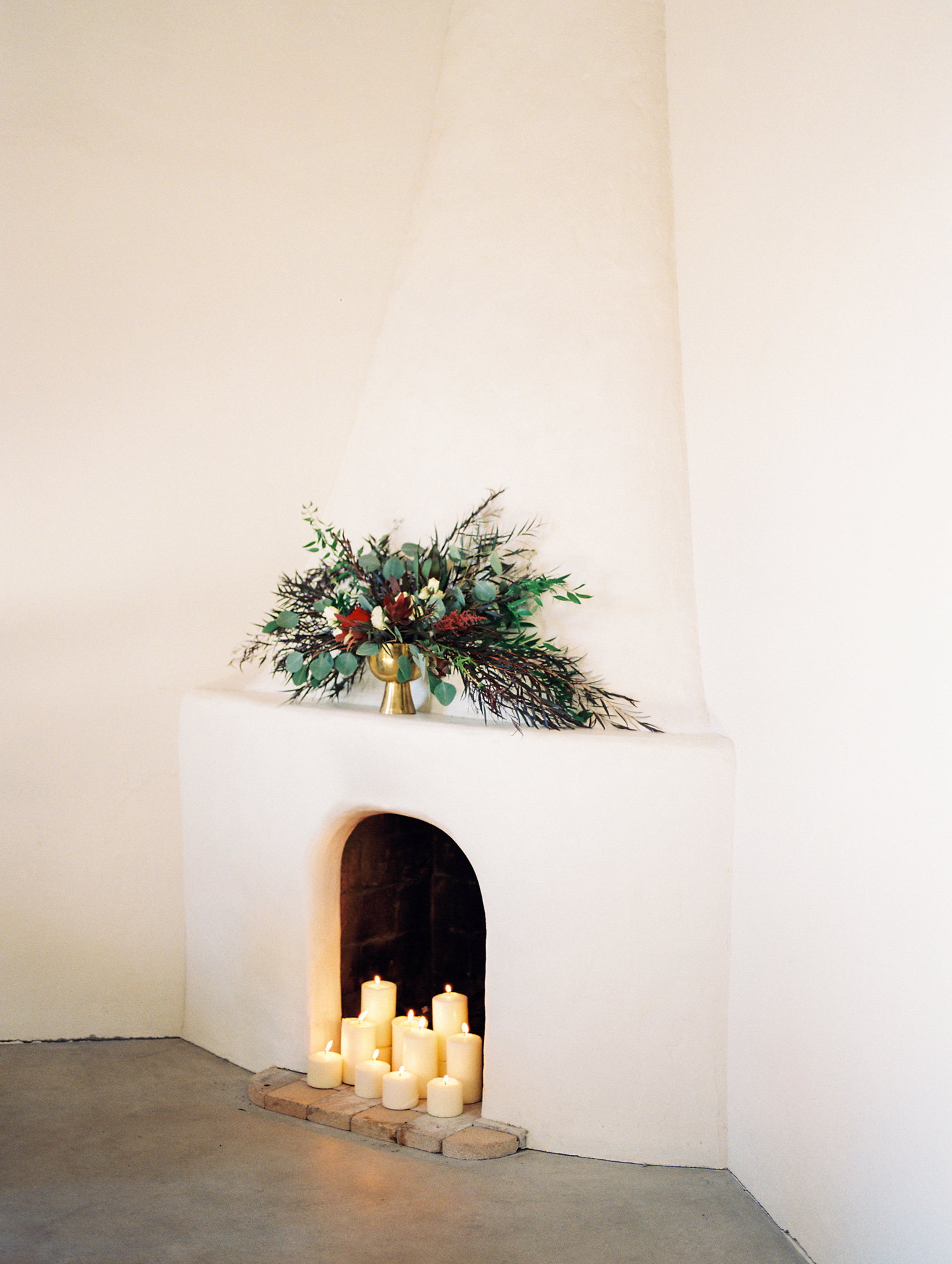 white beehive fireplace with candles burning and wild florals on the mantle